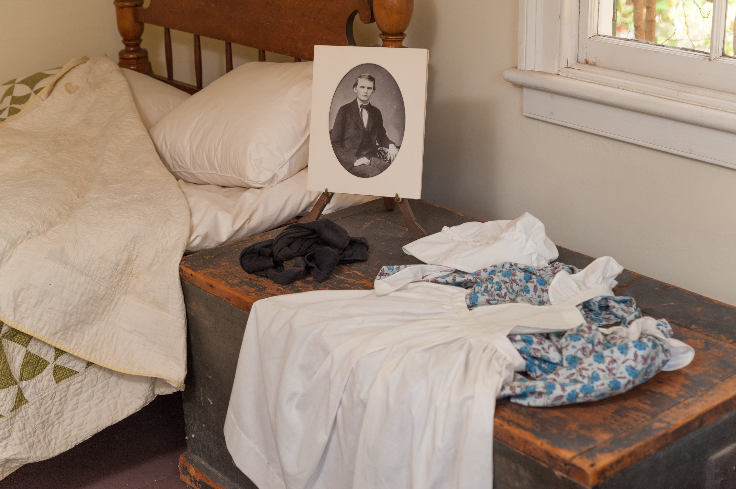 On the cedar chest is a young girls' dress and pinafore apron a well as a picture of one of the Hyatt boys.