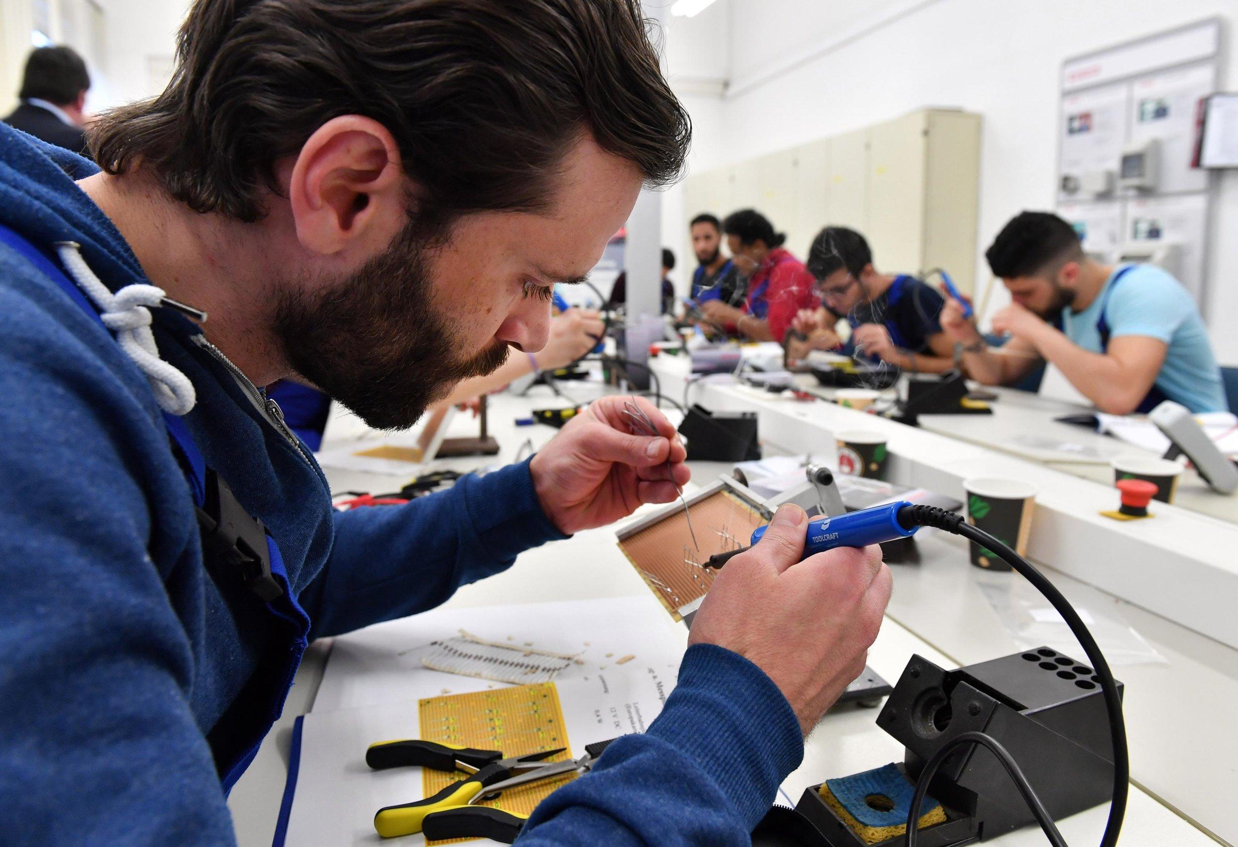 A Syrian refugee at a German Railway training workshop. Image credit:  Quartz