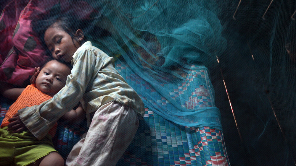 Yonta, 6, rests with her brother Leakhena, 4 months, under a mosquito bed net in the Pailin province of Cambodia. In the first nine months of 2020, the country saw a 70% decrease in malaria cases compared to the same period last year.