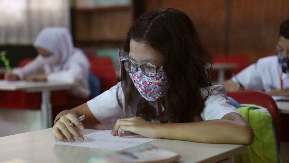 An Indonesian student wears a mask and face shield as a precaution against the coronavirus during a class in Bekasi on the outskirts of Jakarta, Indonesia, 3rd August 2020. Achmad Ibrahim/AP