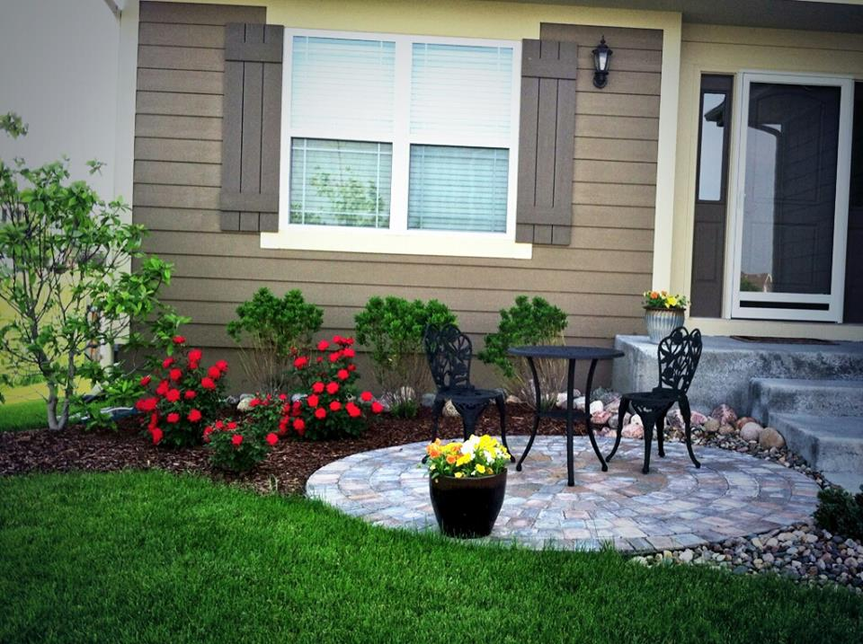 A welcoming landscape in Raymore, MO. Well-structured plants, mixed with colorful roses, and cool circular bistro patio really give this home an inviting curb appeal.