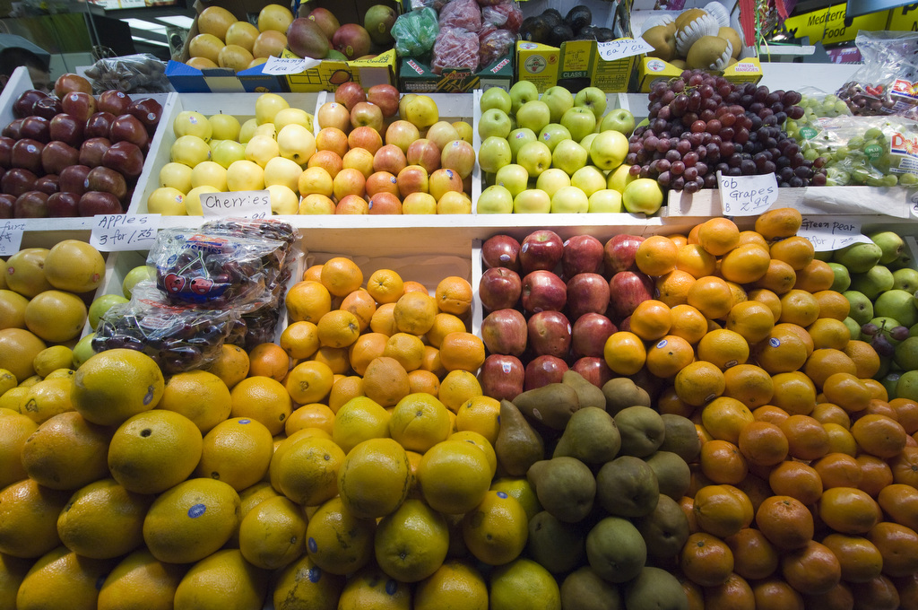 Image by Edwin Remsberg. The photo shows a market table of a variety of fruit, including apples, grapes and oranges.