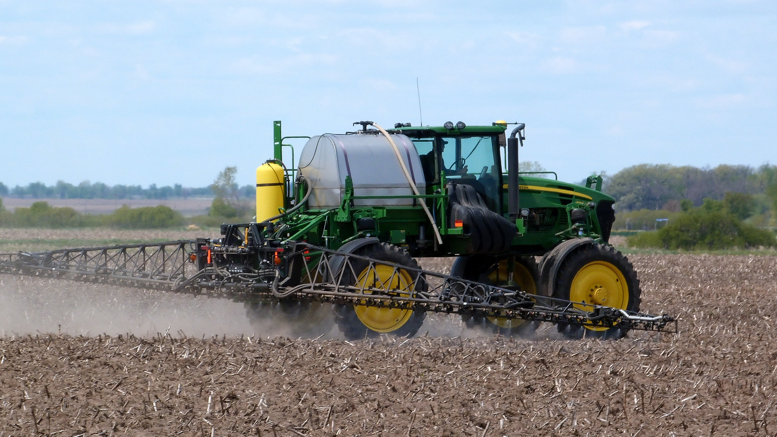 John Deere sprayer while applying a fertilizer and herbicide mix to a field image by Bill Meier