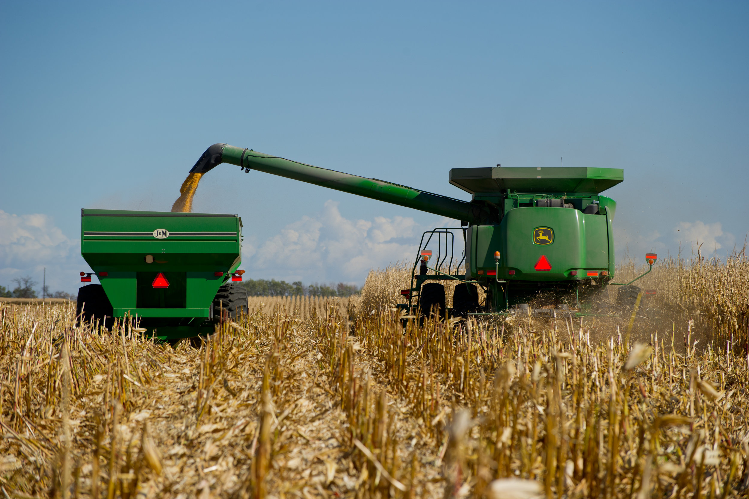 Corn harvest with corn harvester dumping corn into grain cart.  Image is by United Soybean Board