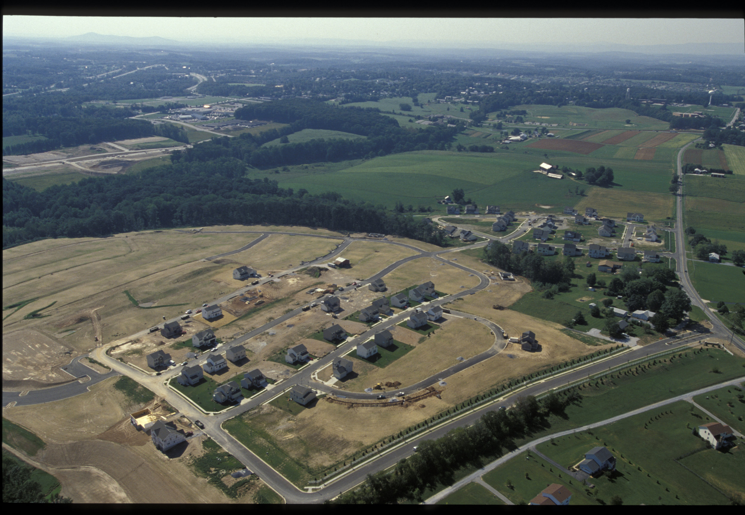 The image shows housing development and farmland in the background. Photo by Edwin Remsberg.