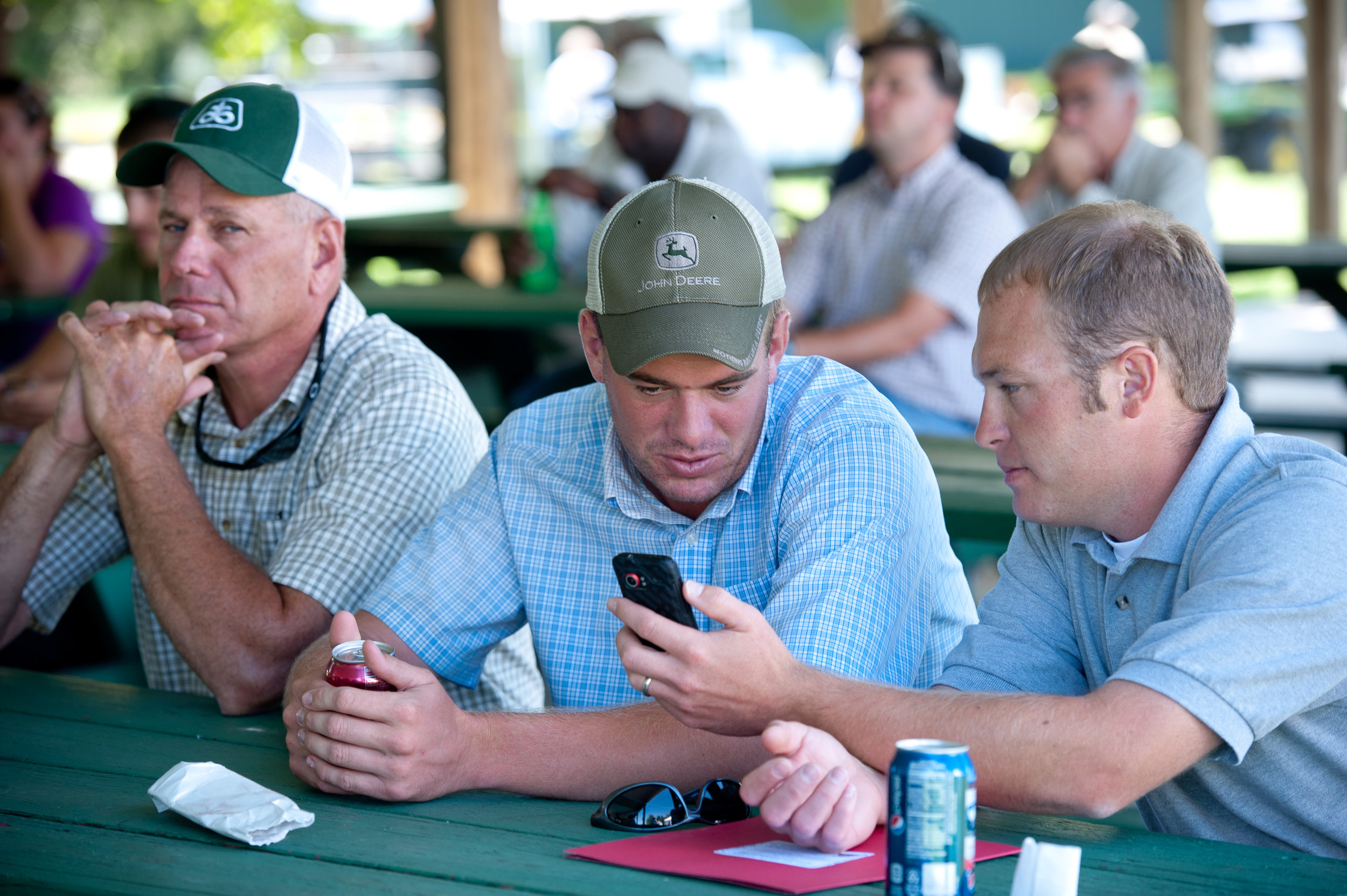 Photo shows men looking at a mobile phone.  Photo credit Edwin Remsberg.