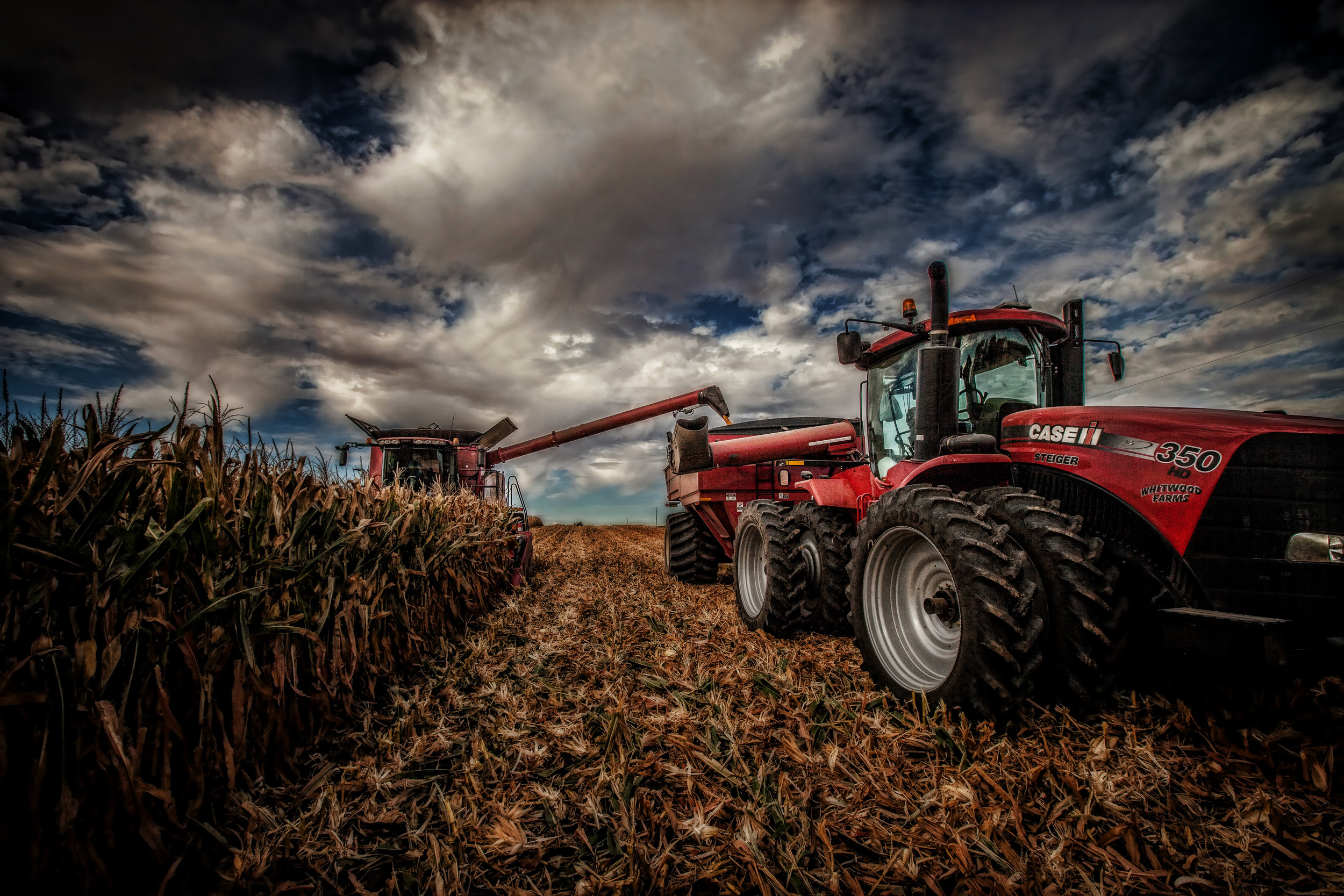 Image of corn being harvested by combine and dumping onto grain cart pulled by tractor.  Image by Steven Baird