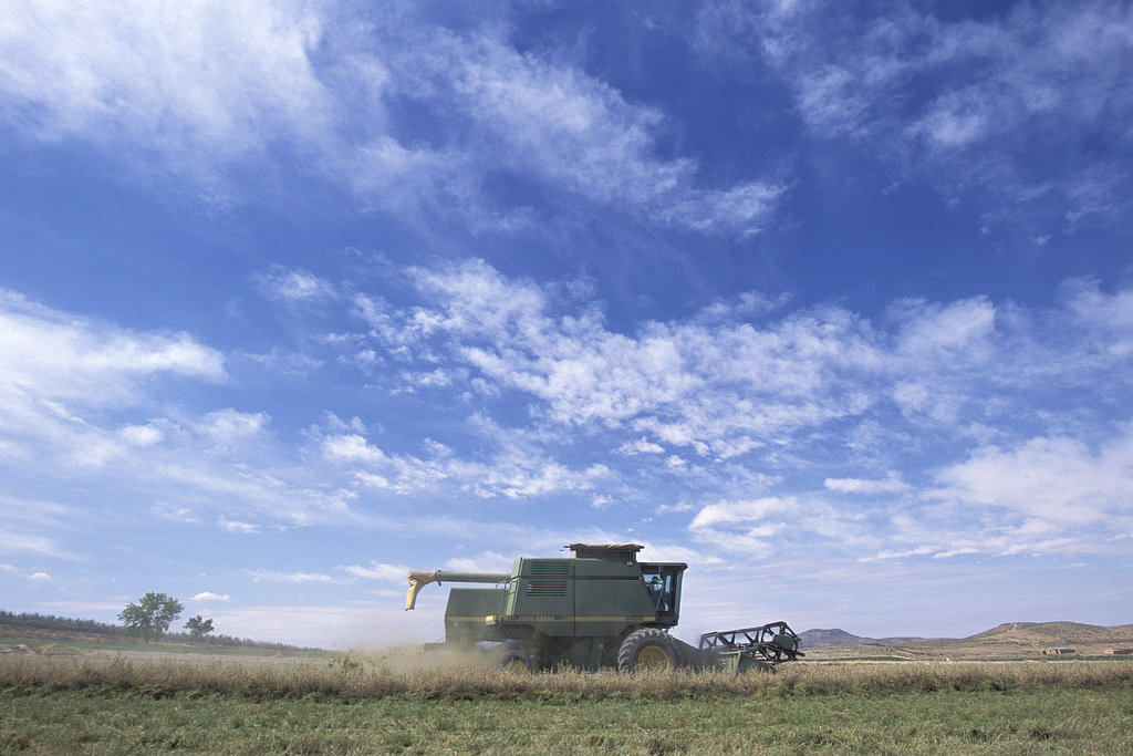 A combine is shown going across a field in this image, taken by Edwin Remsberg.