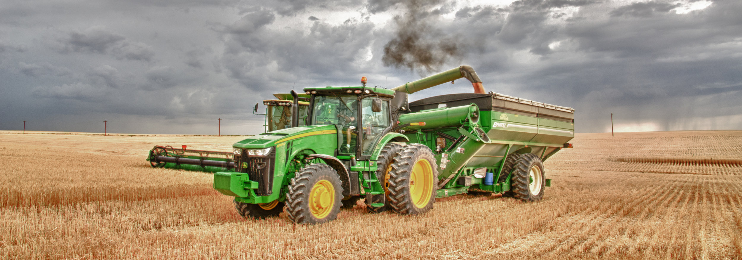 Combine dumping wheat onto grain cart pulled by a tractor. Image is by Shannon Dizmang