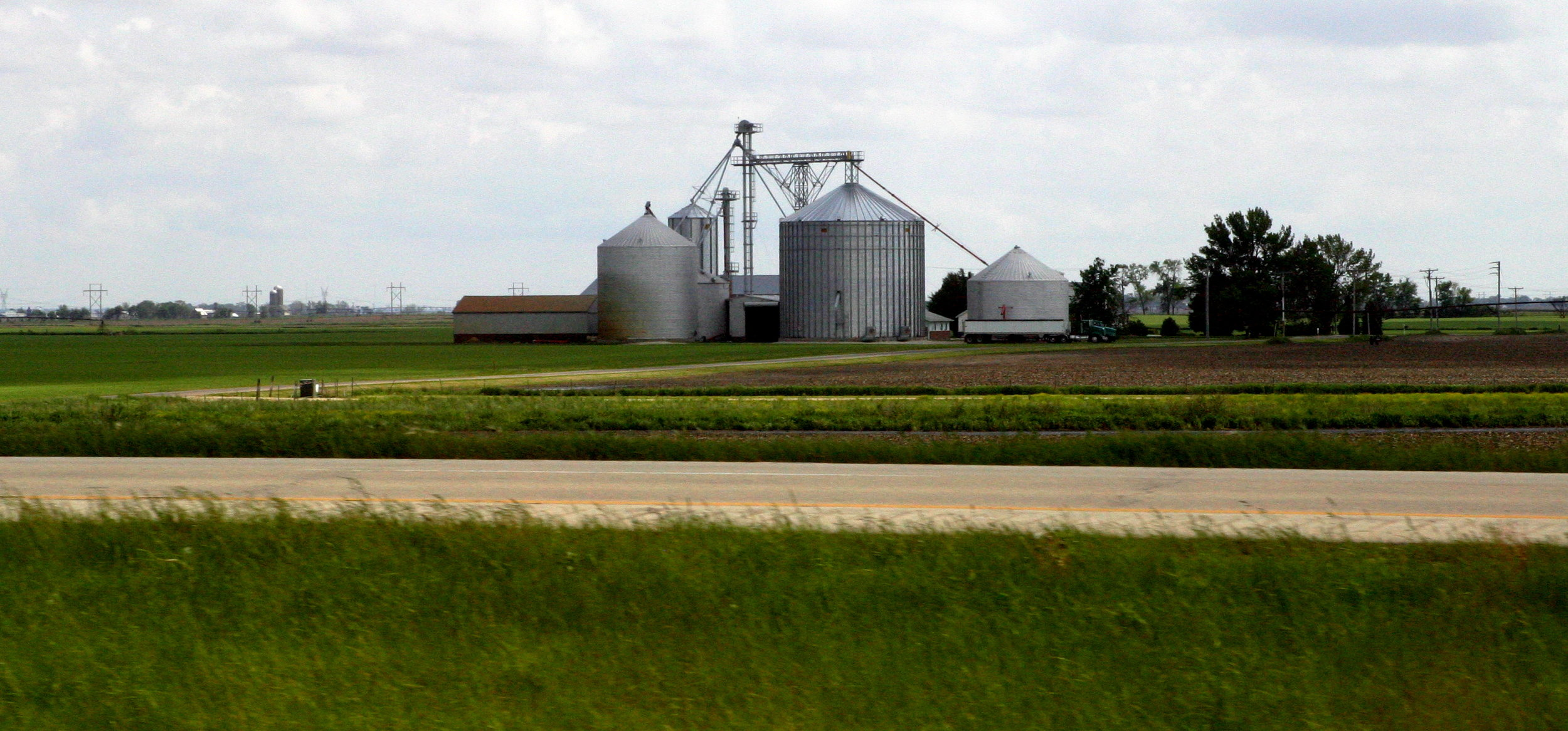 Image of farm with granaries and barn with tilled farmland in foreground.  Image by Camron Flanders.