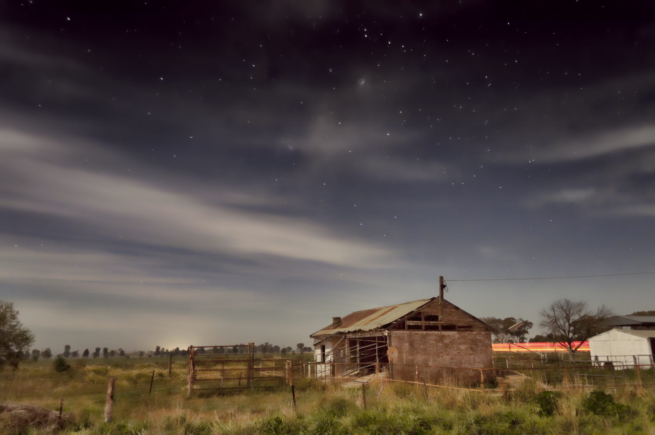 Old farm buildings in a pasture in the moonlight. Image is by Indigo Skies Photography