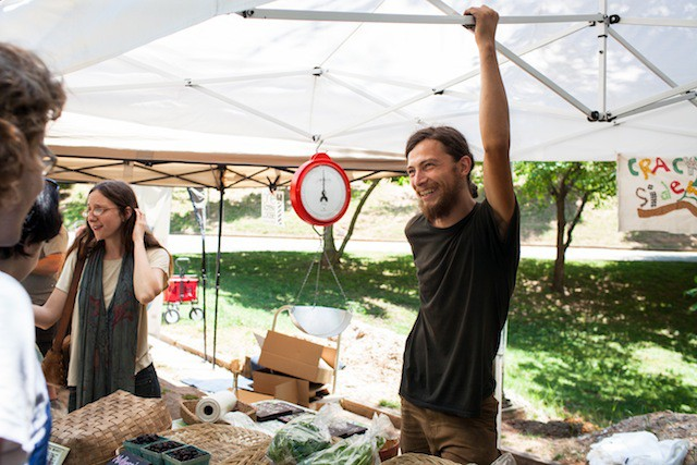 MARKET-ING: Isia Cooper (left) and Chris Clinton of Crack in the Sidewalk Farmlet sell veggies at the Grant Park Farmers Market.
