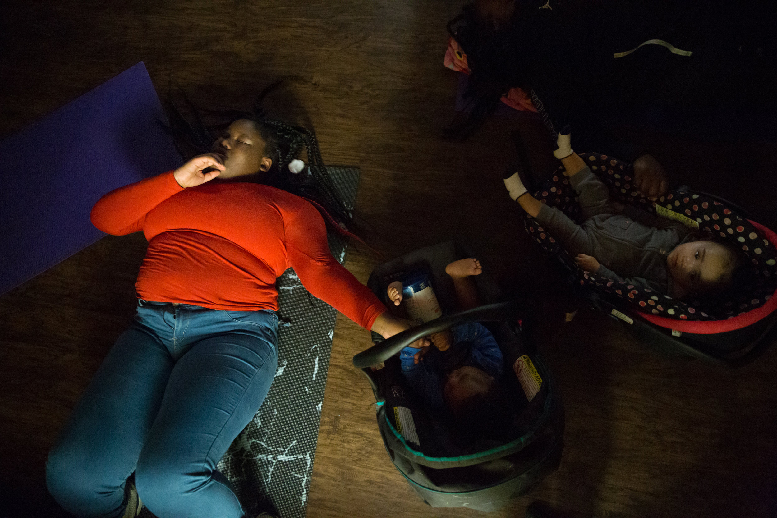 """Mikelah relaxes at the end of a yoga class on Sunday, Oct. 14, 2018. """"It makes you forget about everything else in the world. Then you open your eyes, get up, and it's like… dang."""" The free class is offered weekly at Star House, a center for homeless youth in Columbus, Ohio, that Mikelah's friends frequent."""
