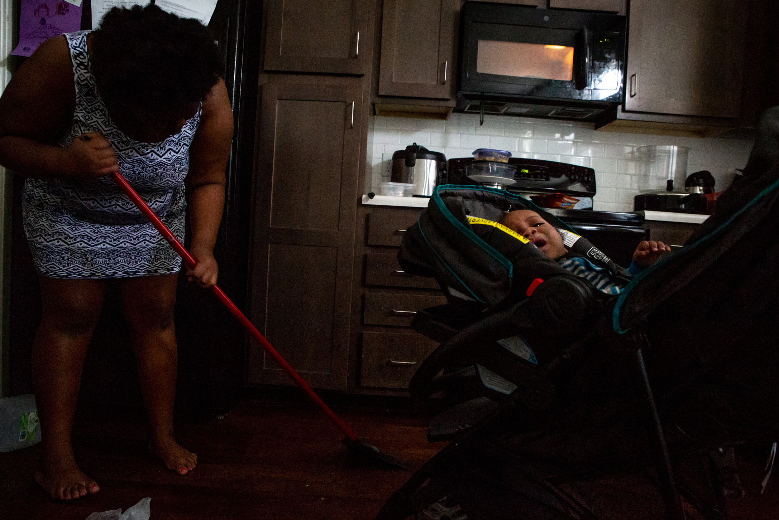 """Mikelah sweeps the kitchen floor next to her son, Isaiah, on Saturday, Oct. 20, 2018. """"I'm like the second mom in here,"""" she said of her responsibilities around the house and taking care of her siblings. Mikelah's stepfather works nights and sleeps during the day, when her mother works as a city bus driver."""