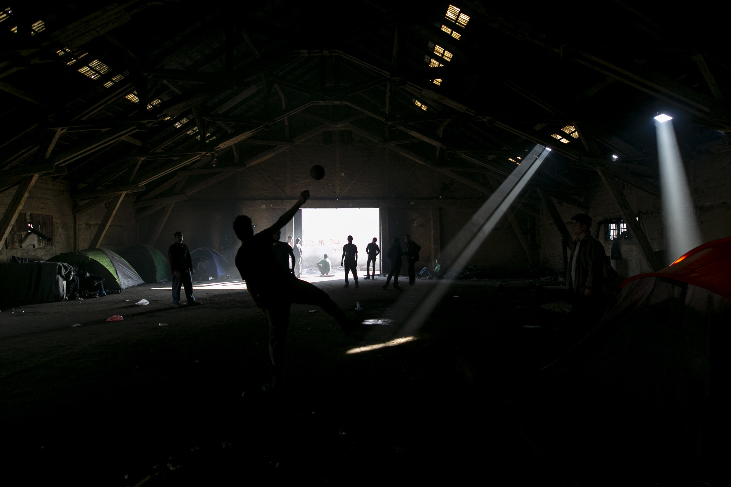 Playing ball in the abandoned warehouse after a majority of refugees were relocated to camp outside of the city. Belgrade, Serbia.