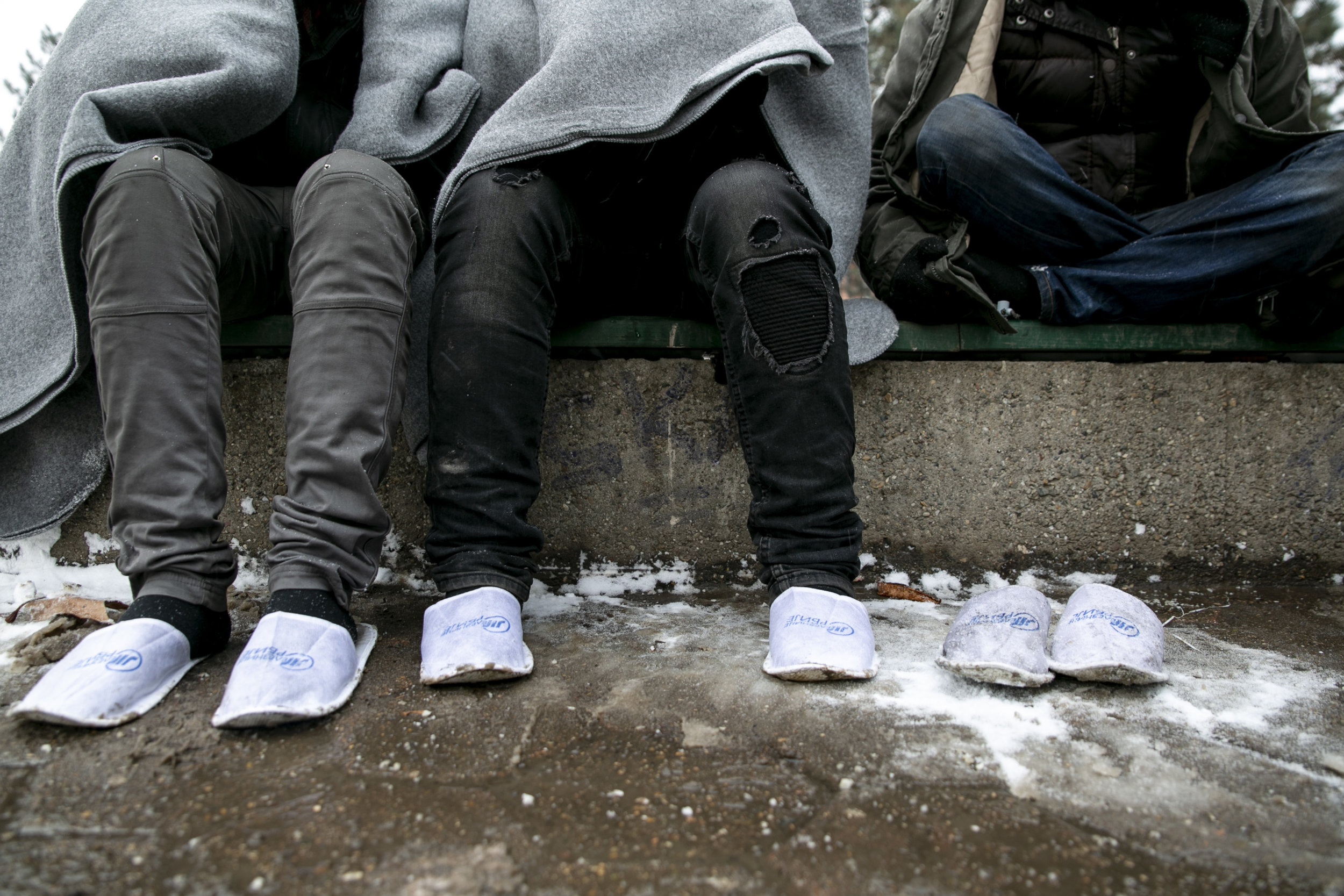 In below-freezing temperatures, paper slippers are supplied to refugees who's shoes were stolen by Hungarian border police. Belgrade, Serbia.