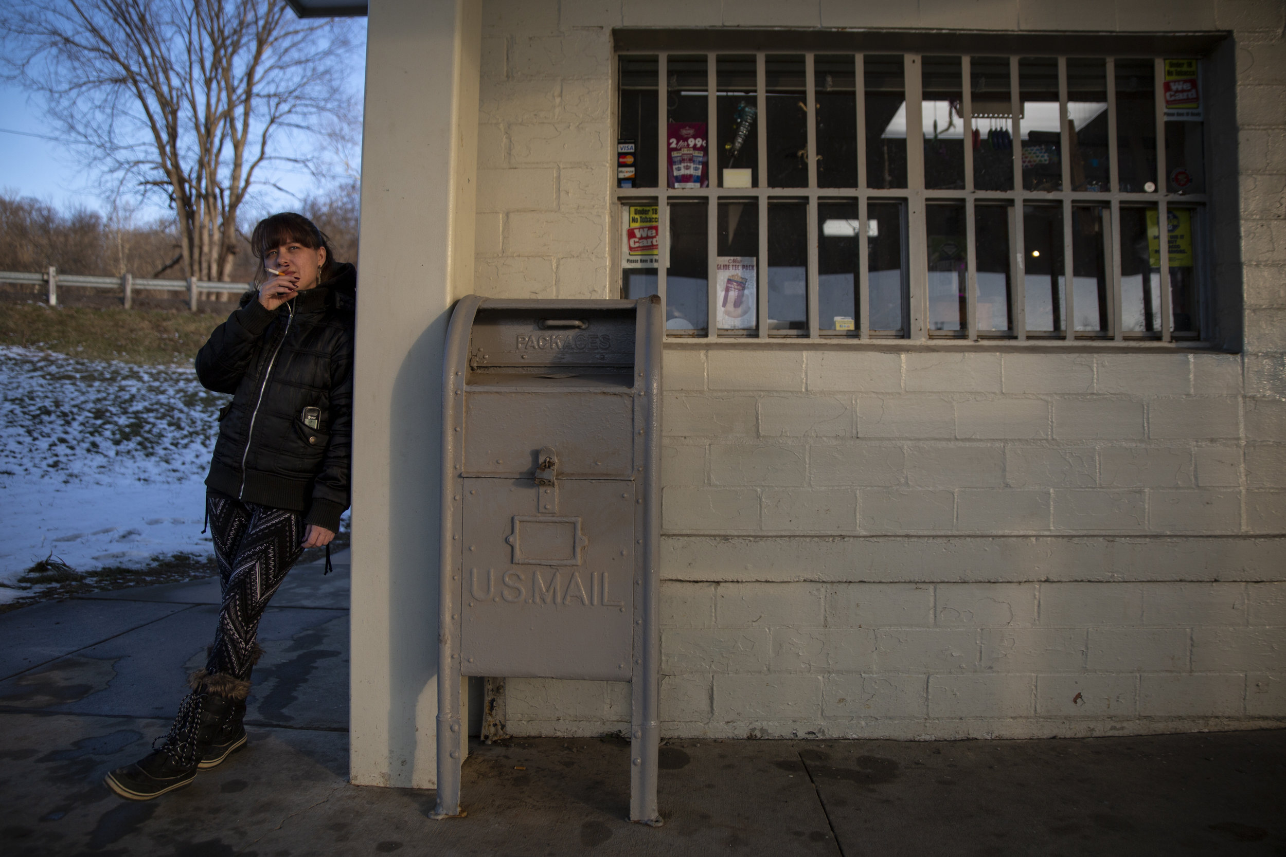 """Brandy Riley takes a smoke break while working at Gilchrist Convenient Store, the only business in the unincorporated community of Sharpsburg, Ohio. This store and gas station also operates as a U.S. Post Office for everyone in the 45777 Sharpsburg zip code. """"This place is like Grand Central Station,"""" said Riley."""