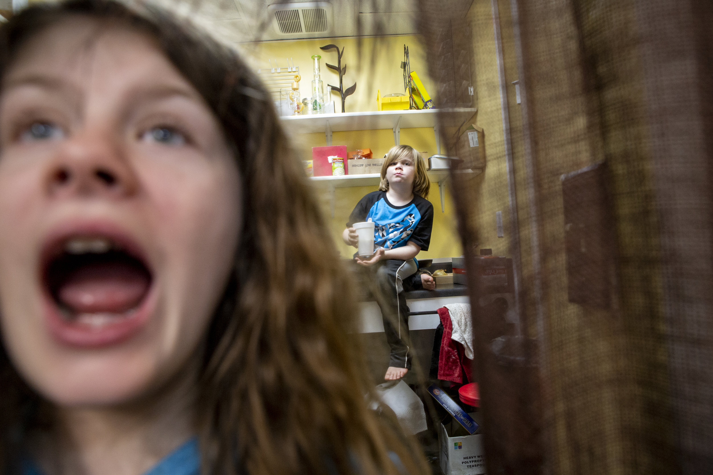 """Siblings Lizzy, 10, and Adam Gilchrist, 6, get ready for school in the back kitchen of Gilchrist Convenient Store every morning. """"They were raised here,"""" said their father Alan Gilchrist, who also grew up playing and working in the family store."""