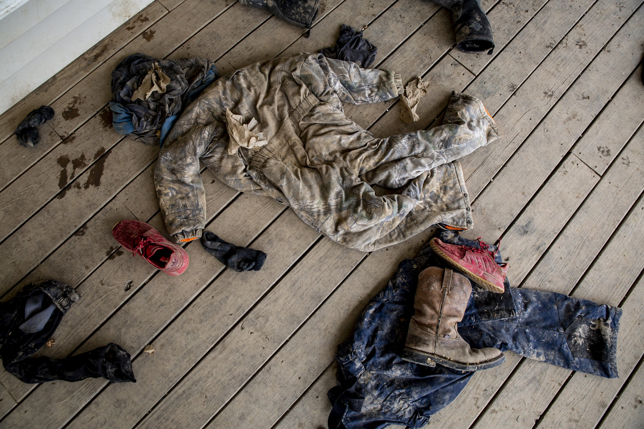 """Muddy clothes adorn the porch of Nick and Tricia Russell's home. """"I can't do a house with a yard and people living next door to me,"""" said Nick Russell, who grew up in Sharpsburg and is now raising his sons there."""