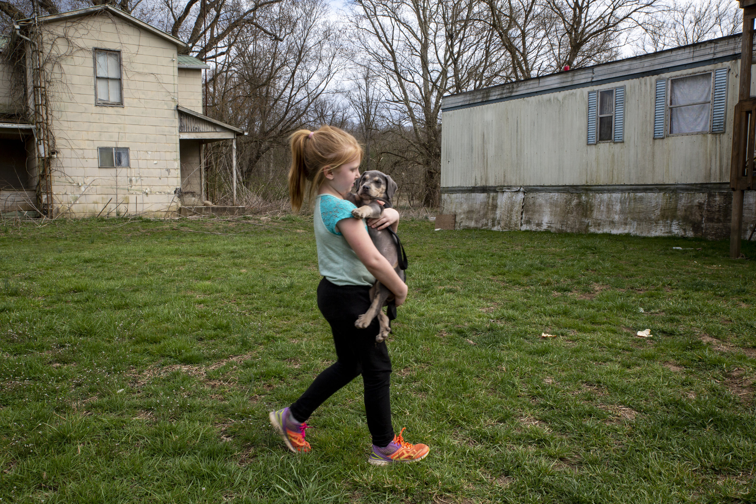 Brooklyn Roof, 6, walks toward her family's trailer holding their new puppy, Chocolate. Many of the community's oldest buildings have been abandoned, but stand alongside the few remaining inhabited homes because it's costly to tear them down.