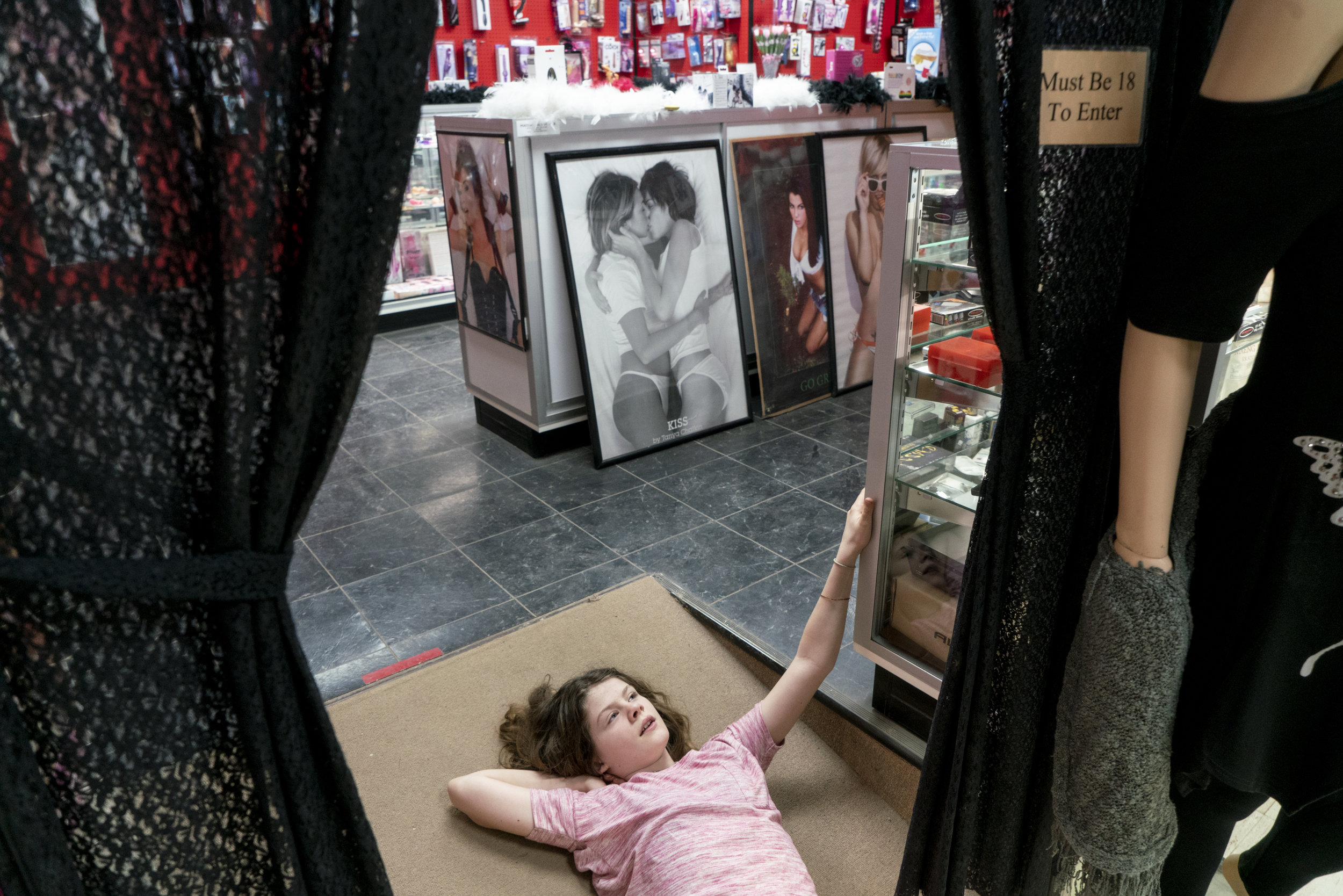 Lizzy Gilchrist, 10, lays in the doorway to the adult only section of her family's shop. Gilchrist Convenient Store sells pipes, CBD products and sex toys, though they don't sell alcohol. The family says their products reflect customer demand, not personal values.