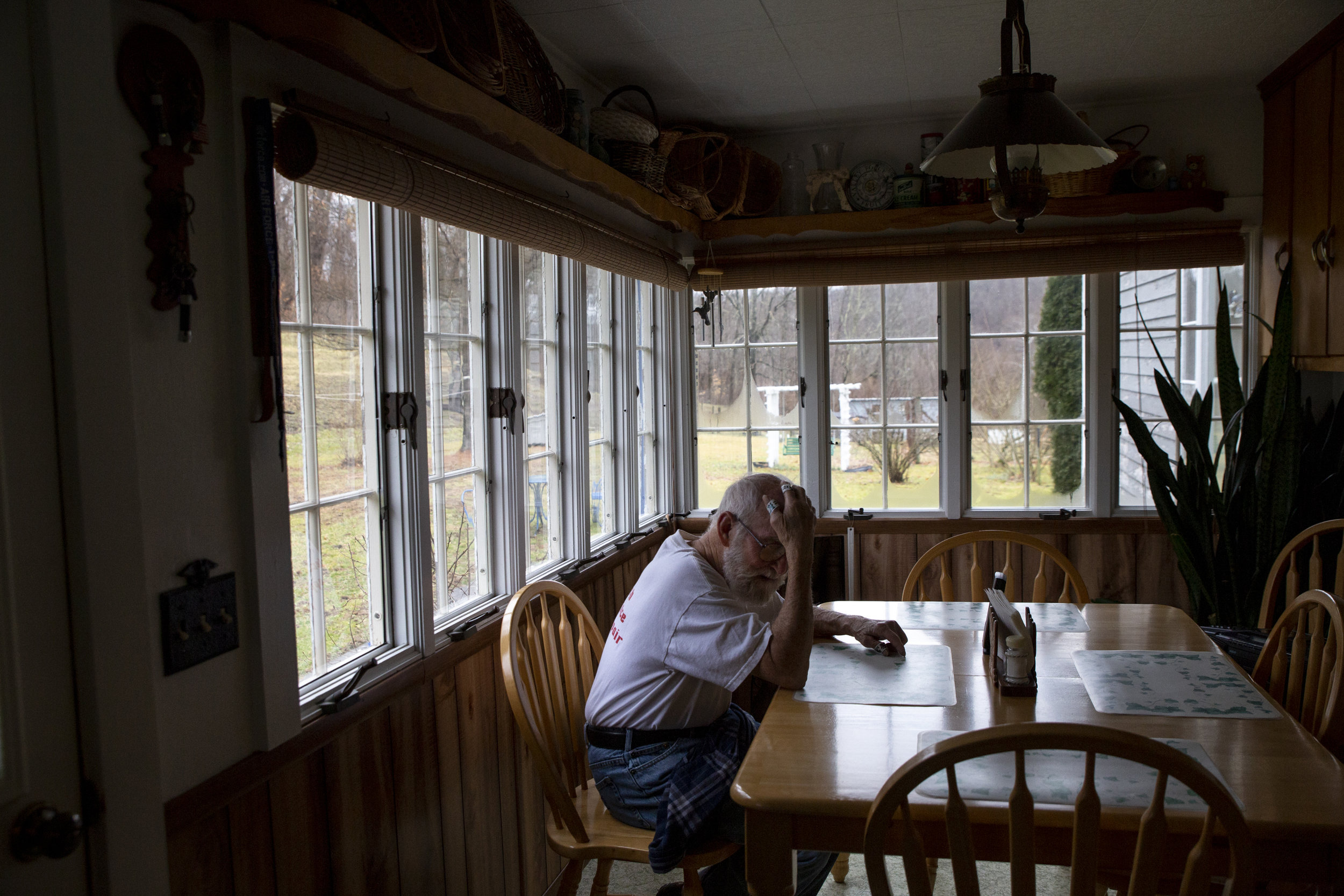 """Bobby Spaulding, 82, rests in his kitchen after feeding his 15 cattle. Although he is battling cancer for a second time, Spaulding continues to raise cattle with his wife in order to afford their home. While he would like to sell the farm, his wife JoAnn says she can't leave because """"it's just home."""""""