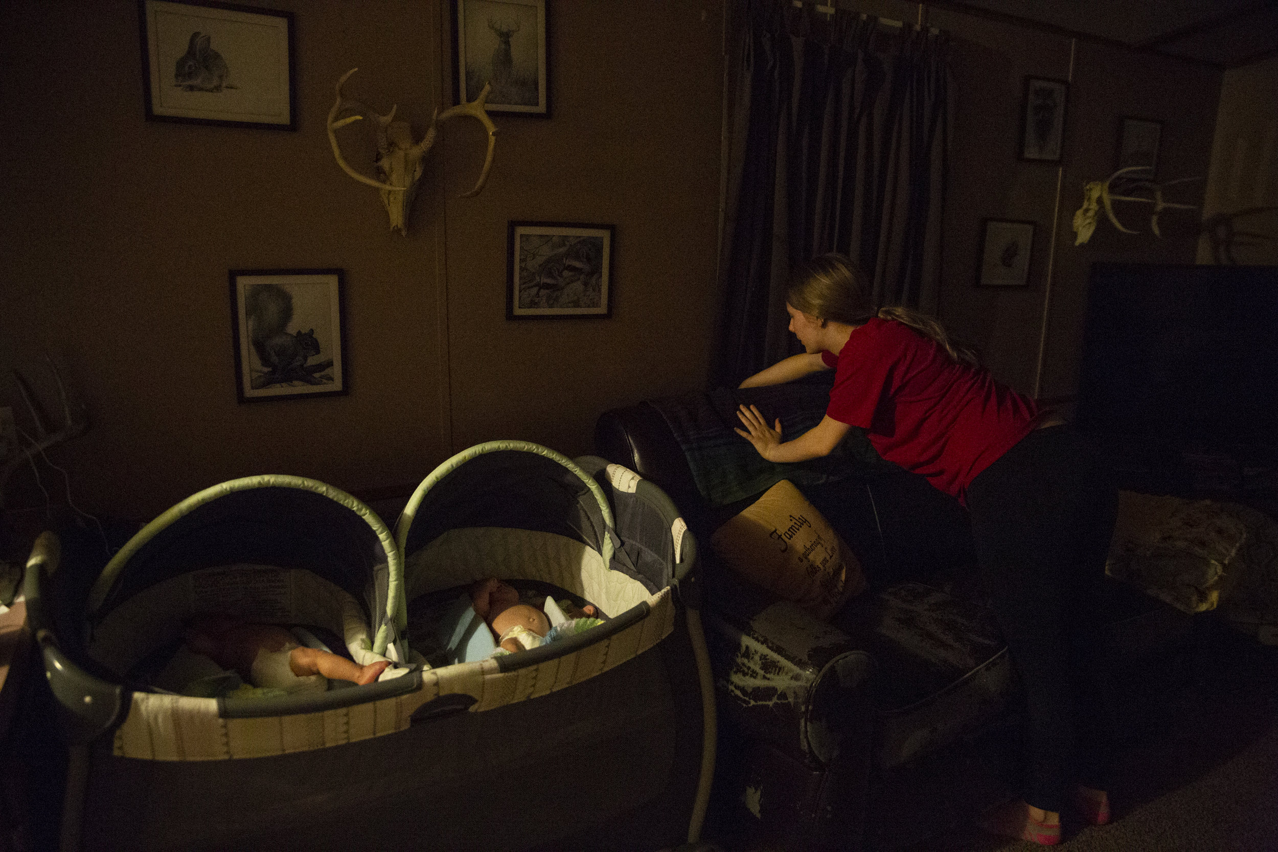 First-time mother April Riley, 19, cleans up at night after her three-month-old twins, Eli and Evan, fall asleep.