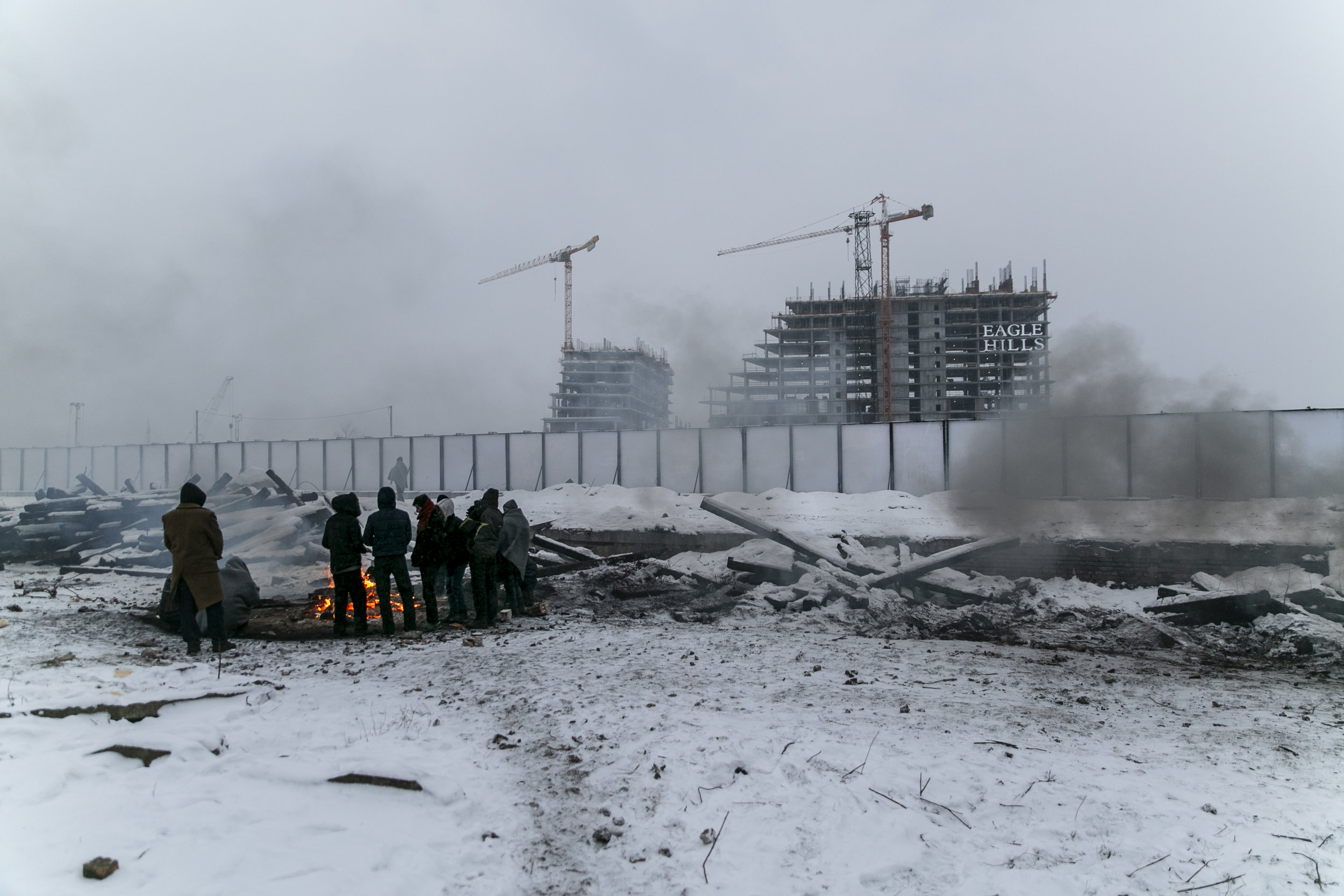 Refugees from Afghanistan and Pakistan warm themselves by a fire made from chemically treated railroad wood on Jan. 10, 2017 in Belgrade, Serbia. Across the fence, a private Abu Dhabi-based real estate company, Eagle Hills, constructs luxury apartments as part of the 4-billion-dollar Belgrade Waterfront project.