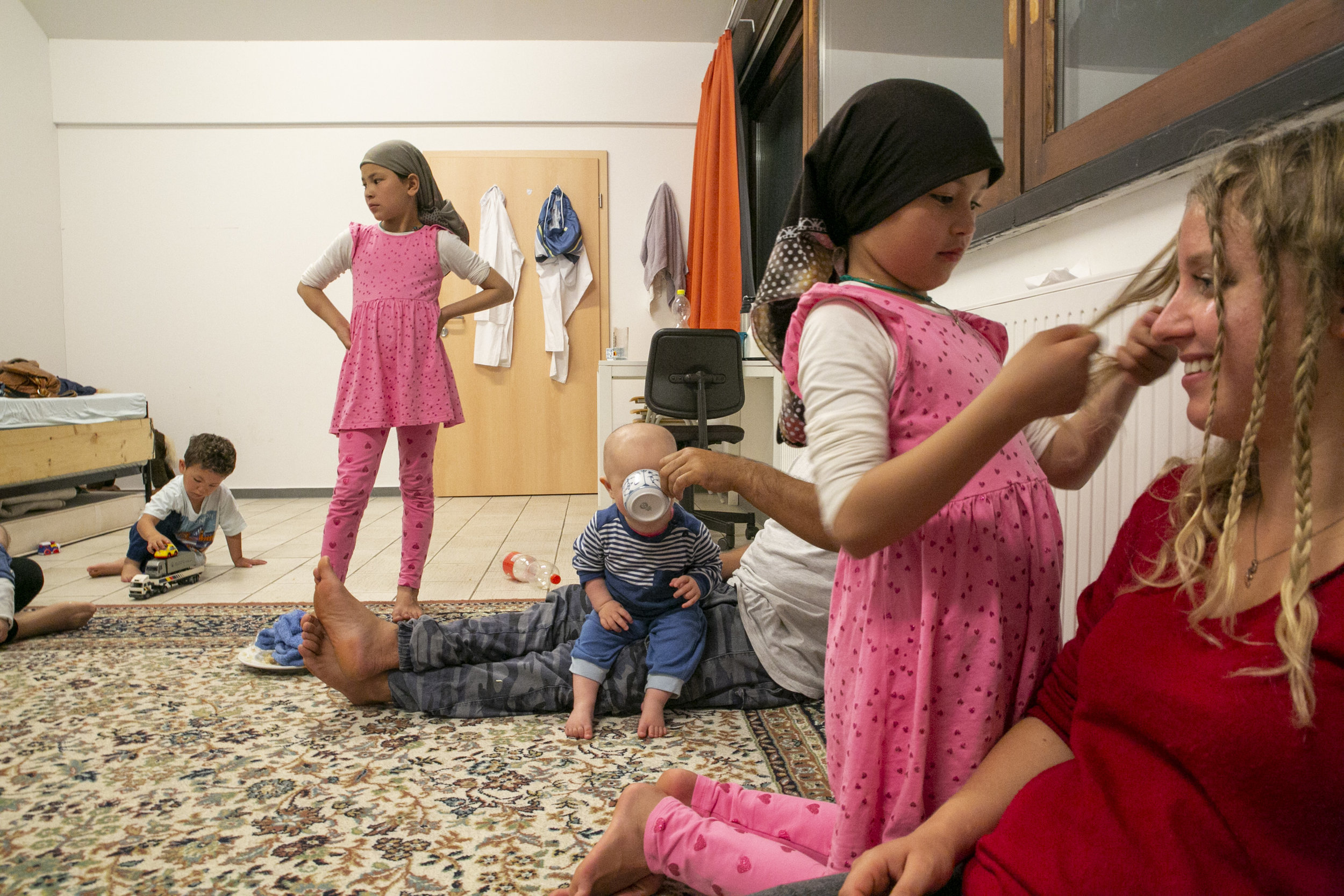The Noori family traveled on foot from Afghanistan to Serbia in 2016, where they developed a strong bond to Diana Vasov, a 24-year-old aid worker in Belgrade. Like their daughter Donia, center, Vasov, right, was also born in a refugee camp after her family fled Yugoslavia in 1991. Here, Vasov visits the Noori family on June 29, 2017, in Germany, where they were granted asylum in 2017.