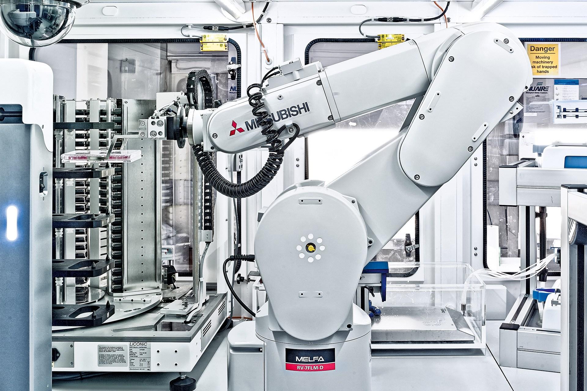"""Robot Mitsubishi pour """"salle blanche"""" exerçant dans un domaine médical,les modèles pour salles blanches se distinguent des robots standard par leur surface spécialement vernie et polie afin d'empêcher les dépôts de particules. Des joints modifiés permettent aussi d'éviter l'abrasion. Ces finitions sont nécessaires àl'installation des robots dans des environnements critiques propres àl'industrie alimentaire ou pharmaceutique.  Photographie:  Christoffer Rudquist"""