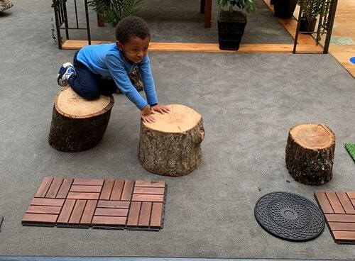 Children have been using the wood stumps to balance while going from one stump to the other. They try balancing while standing or crawling, as seen in the picture.  Children also use the stumps to sit on and take a break or have conversations such as during dramatic play.  Children have been exploring the stump sides and feeling different textures and edges.