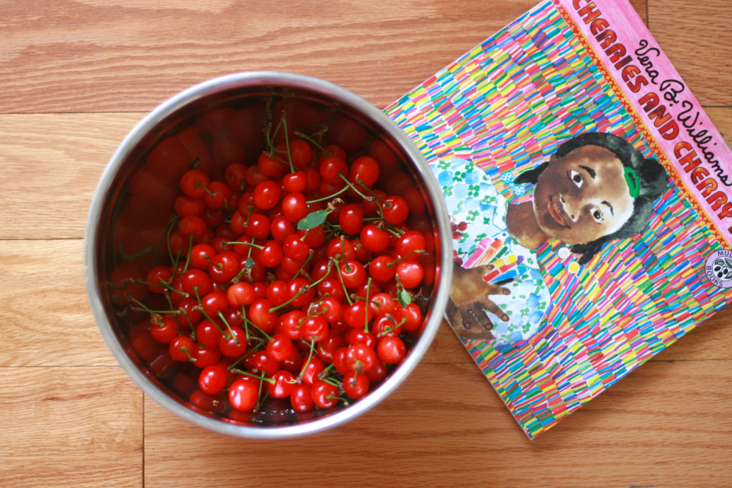 Some of our backyard cherry spoils, plus our family's favorite cherry-themed book,  Cherries and Cherry Pits