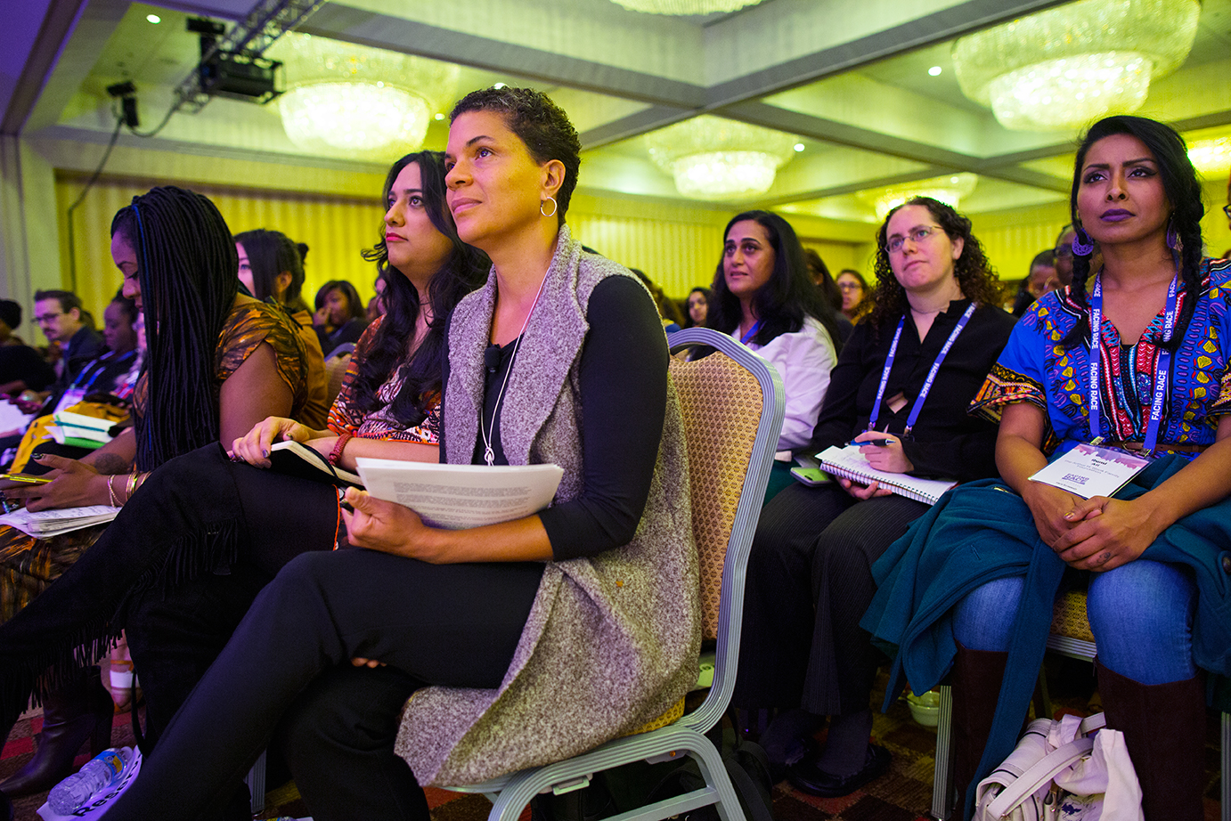 """Michelle Alexander (third from left;  The New Jim Crow ) and other conference attendees listen to a speaker at Facing Race 2016 before the plenary session, """"Multiracial Movement for Black Lives."""" To her right are Isa Noyola ( Transgender Law Center ) and Alicia Garza ( National Domestic Workers Alliance  and #BlackLivesMatter), Atlanta, GA, 11 November"""