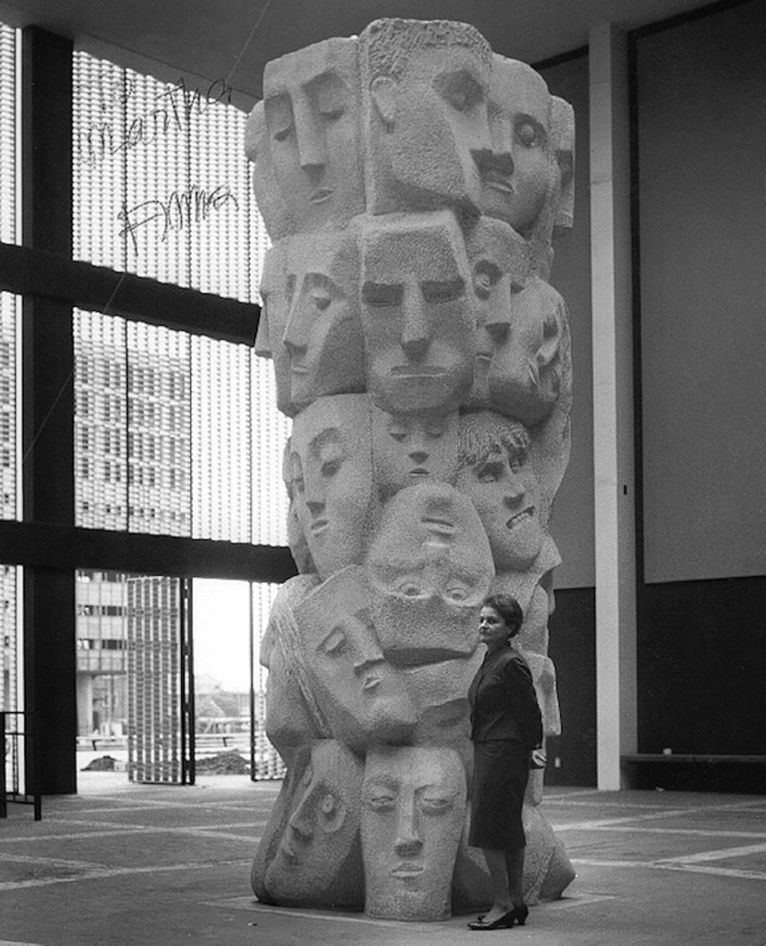 """The artist standing next to her work """"Tower of Masks"""" which is part of the UCLA sculpture garden."""