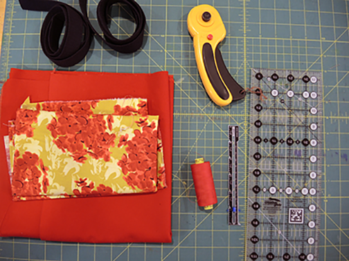Materials clockwise from top: rotary cutter, omni-grid ruler, seam gauge, thread, fabric, webbing