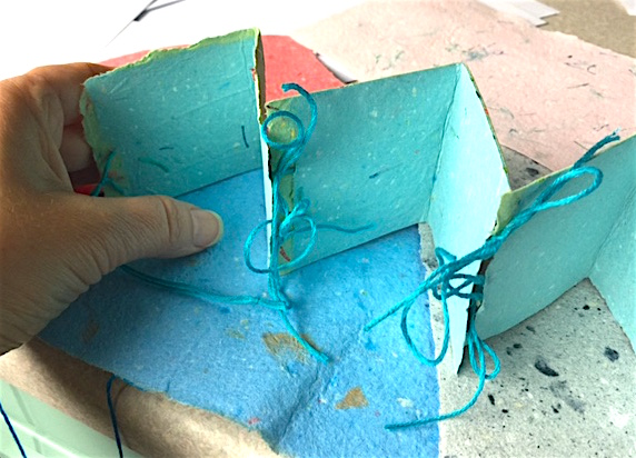 Decorative book: Layer two sheets,sandwiching string between sheets of wet pulp. Cut and assemble when dry.