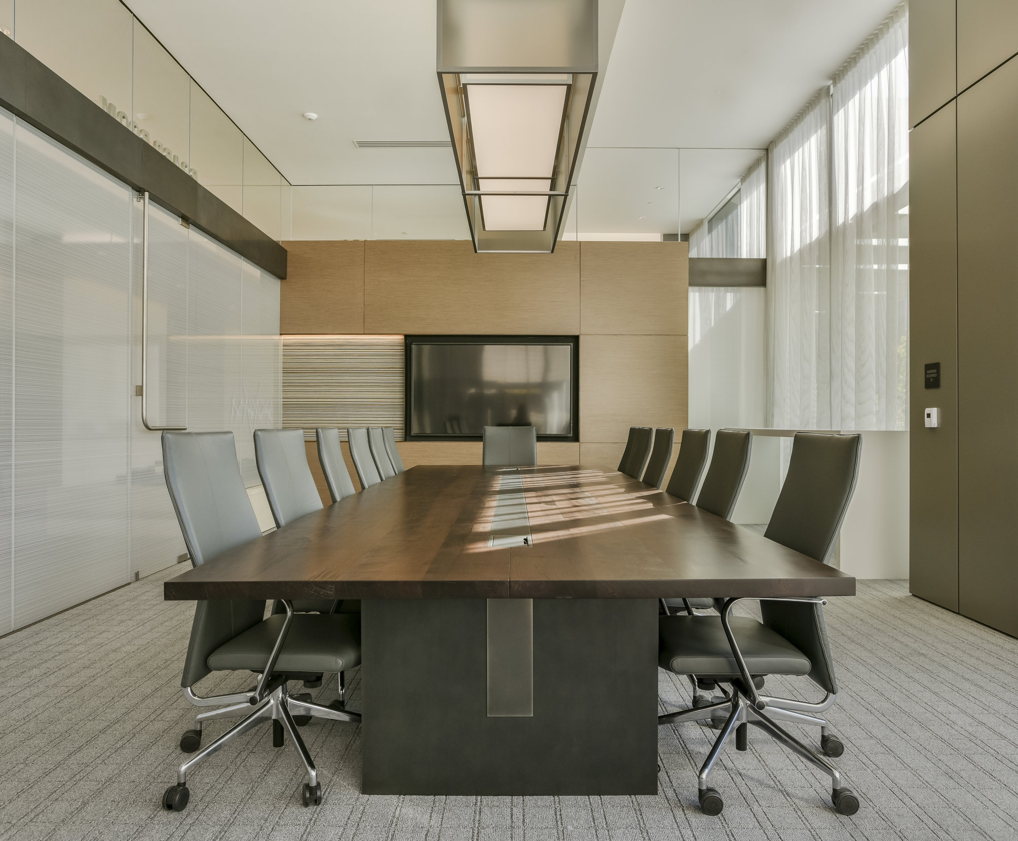 Custom Maple conference table with steel inlay in top and base, data units at both ends