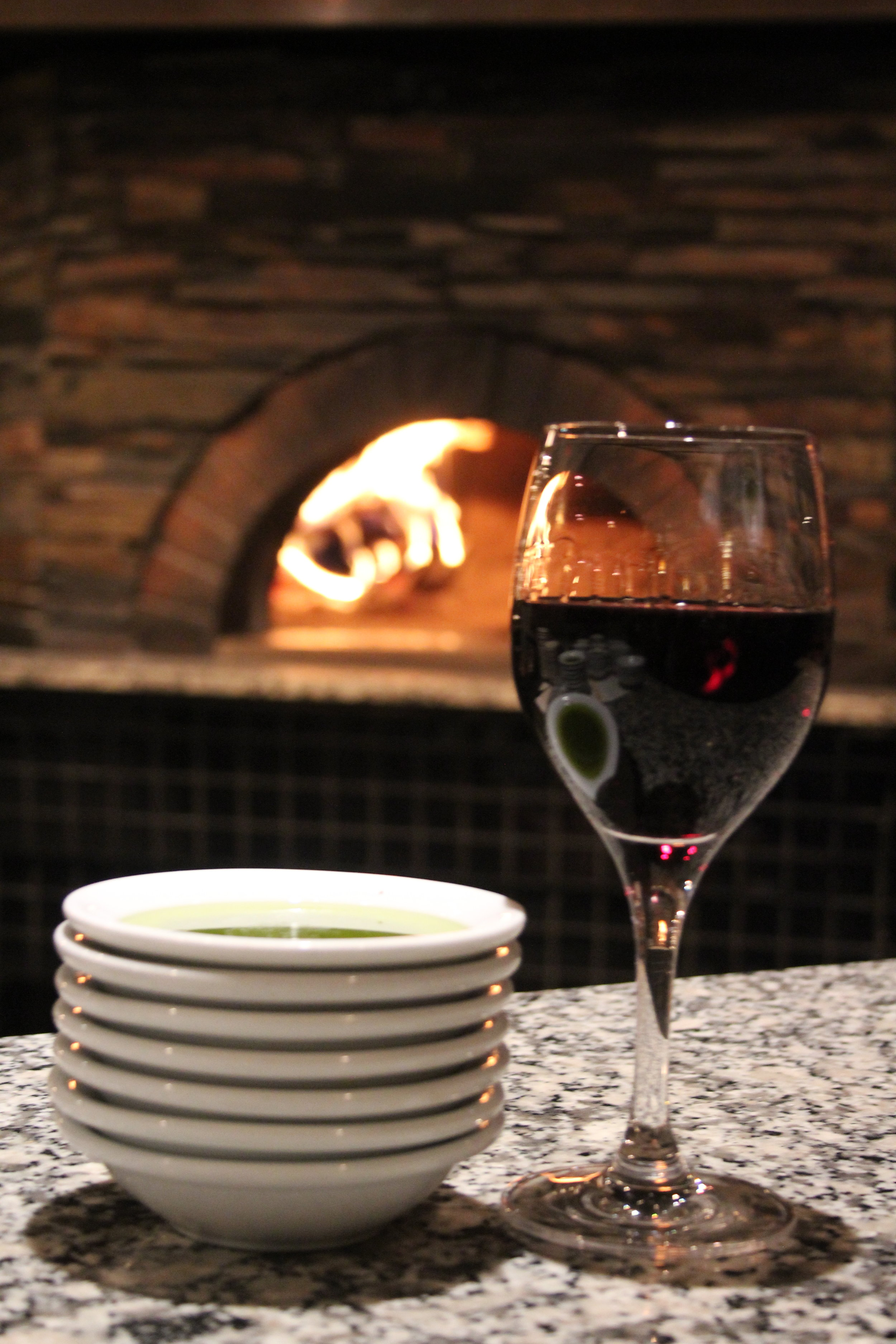 Wine glass next to bowl with green liquid with fire in the background.JPG