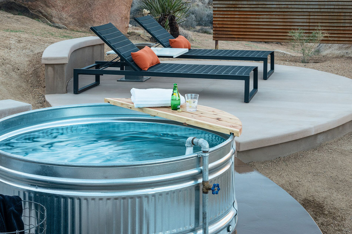 """Cowboy Tubs - We were among the first in the High Desert to create """"instant swimming pools"""" by converting galvanized steel stock tanks to """"cowboy"""" tubs. In hot weather, renters are delighted to find a place to cool off. Cowboy tubs fill that bill economically and have the added advantage of being""""Instagrammer magnets.""""We convert stock tanks so that they have a rapid-fill capability and a quick-drain system. The idea is not to store water in them (as with a swimming pool or hot tub), thus avoiding the need to have them serviced. Instead they are  drained after each use into underground perforated pipe that is installed  adjacent to plants that can benefit from a little  extra water.We have installed both round tanks (usually five or six feet in diameter) and smaller, oblong ones."""