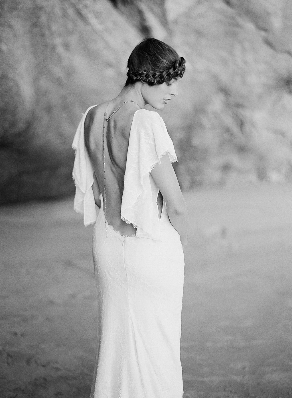 bride poses on the beach in her Dress Theory Gown and crown braid at this oregon coast wedding photographed by destination wedding photographer Lexia Frank -a film photographer in Portland oregon.