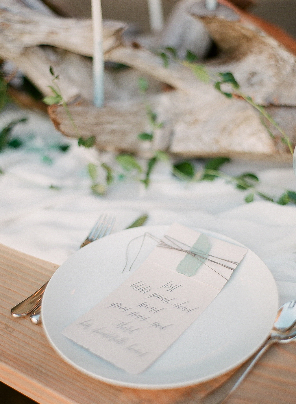 a calligraphed menu by Gracelineart.com with seaglass at a beautiful beach tablescape at this oregon coast wedding photographed by destination wedding photographer Lexia Frank - a film photographer in portland oregon. TOP DESTINATION WEDDING PHOTOGRAPHY, OREGON COAST WEDDING, WWW DOT LEXIA FRANK DOT COM