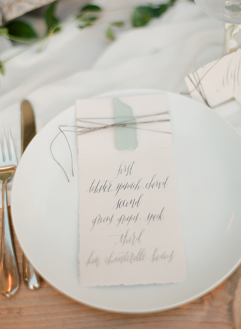 a hand calligraphed menu by Gracelineart.com and seaglass accents for this tablescape at the oregon coast wedding photographed by destination wedding photographer LExia Frank- a film photographer in portland oregon. TOP DESTINATION WEDDING PHOTOGRAPHY, OREGON COAST WEDDING, WWW DOT LEXIA FRANK DOT COM
