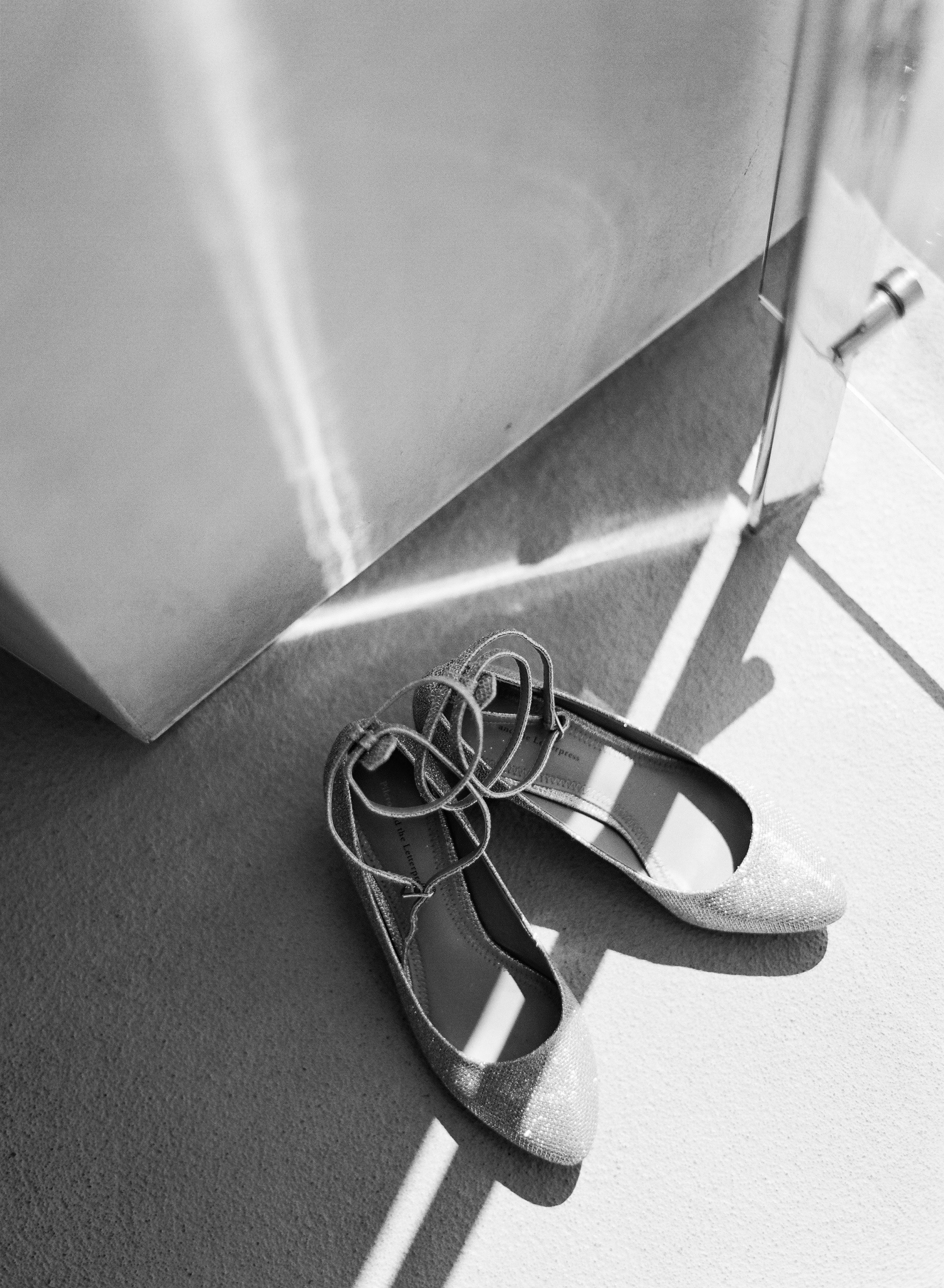 destination wedding photographer shoots orthodox jewish wedding and bride's wedding shoes in black and white film photography
