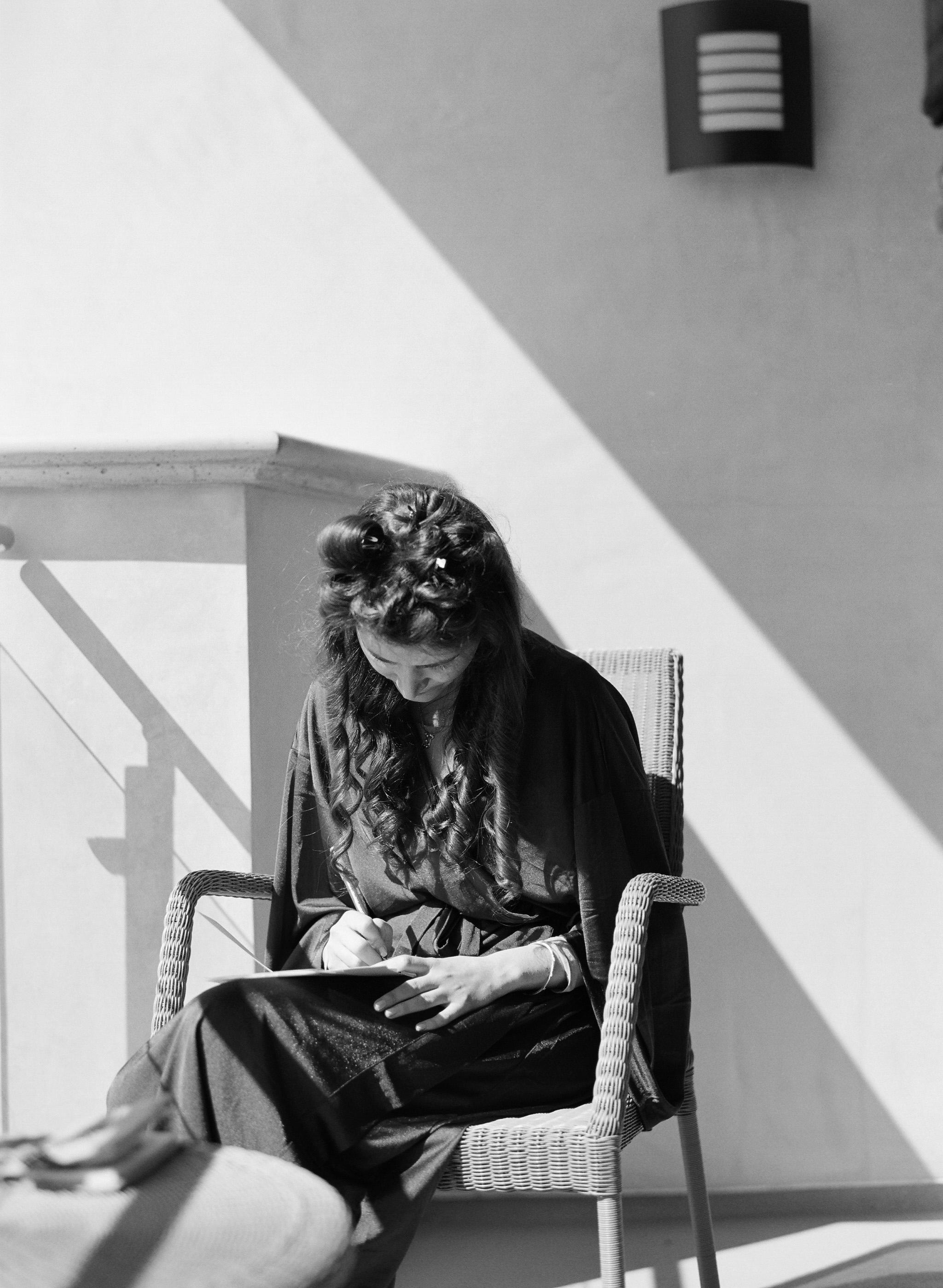orthodox jewish bride writes vows at her destination wedding in malibu. black and white film photography