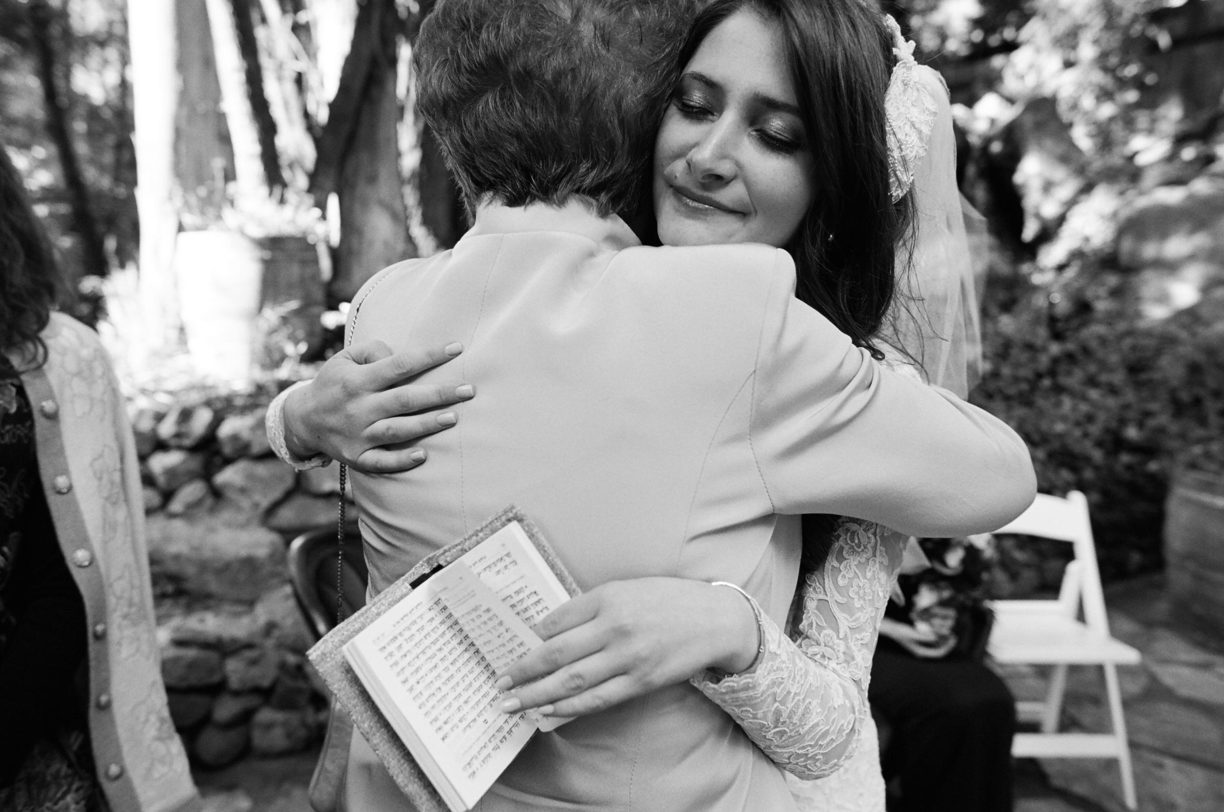 best destination wedding photographer photographs malibu wedding with orthodox jewish bride hugs grandmother while holding biblical text.