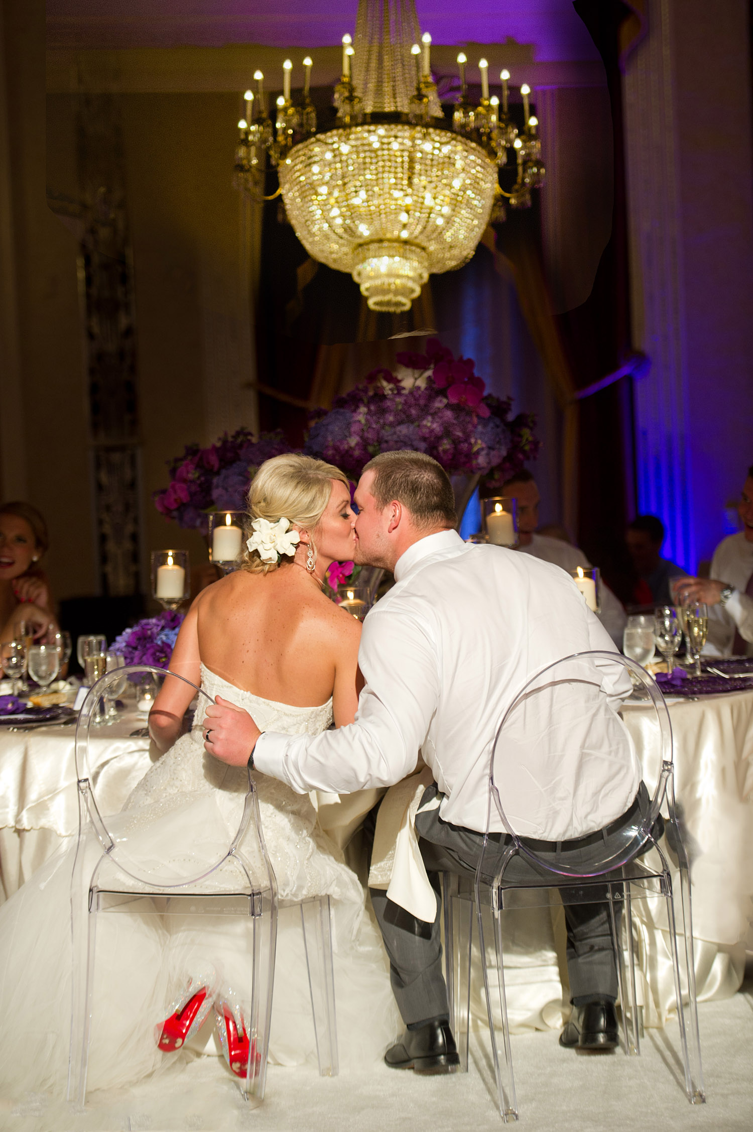 TOP DESTINATION WEDDING PHOTOGRAPHER LEXIA FRANK PHOTOGRAPHS PRO FOOTBALL PLAYER GREEN BAY PACKER BRYAN BULAGAS WEDDING AT THE HILTON CITY CENTER IN DOWNTOWN MILWAUKEE. LUCITE CLEAR CHAIRS WITH PURPLE FLORAL  AND LOUBOUTIN BRIDAL SHOES
