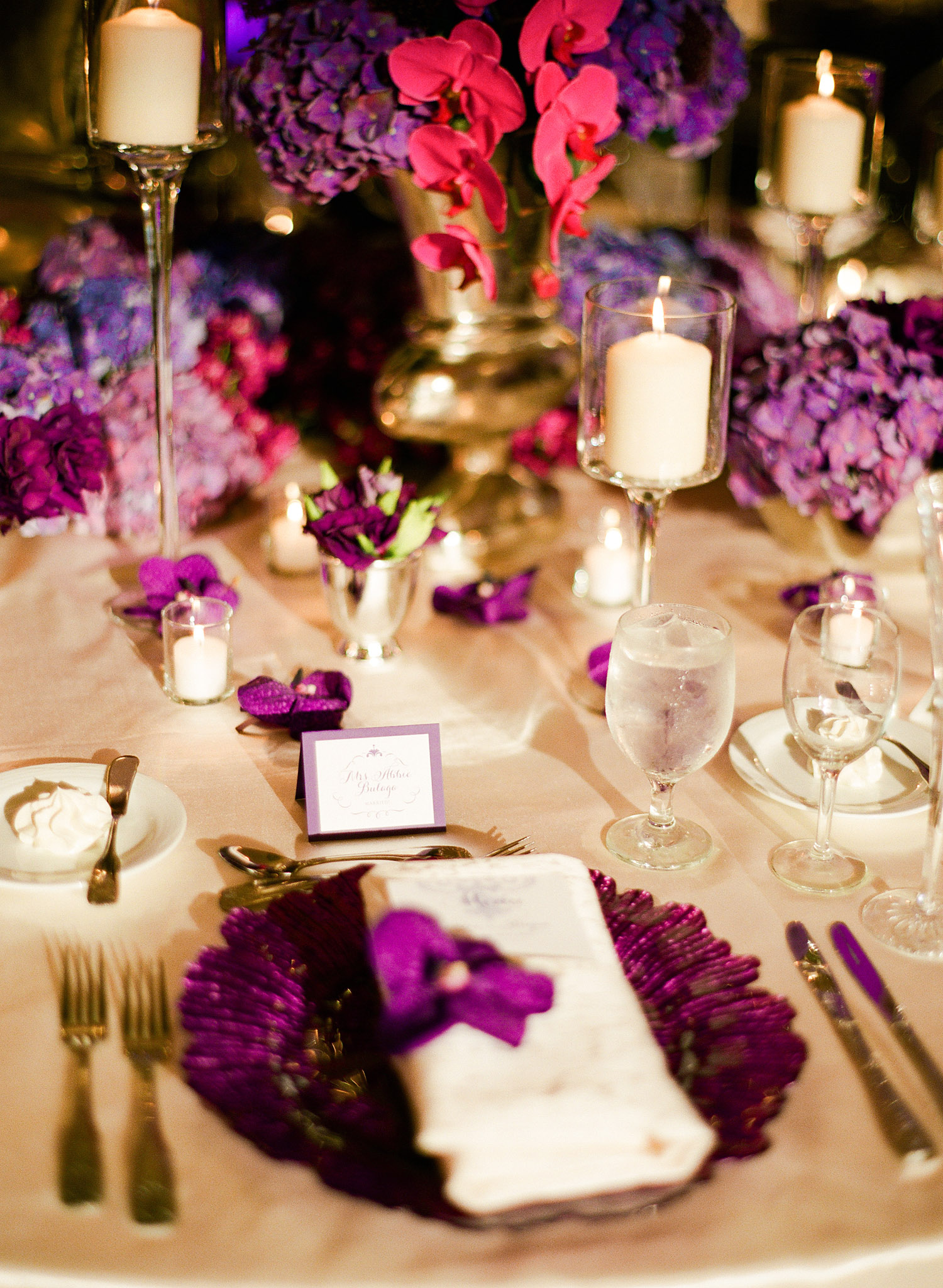 DESTINATION WEDDING PHOTOGRAPHER LEXIA FRANK PHOTOGRAPHS PRO FOOTBALL PLAYER BRYAN BULAGA OF THE GREEN BAY PACKERS WEDDING AT THE HILTON CITY CENTER IN MILWAUKEE WISCONSIN. RECEPTION PLACE SETTINGS PURPLE WITH GOLD SHOT ON FILM
