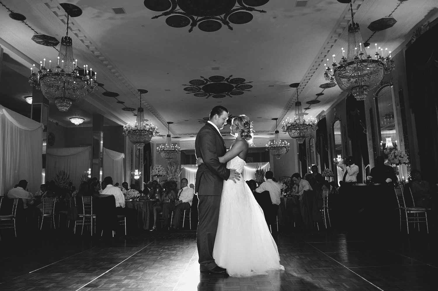 PRO FOOTBALL PLAYER BRYAN BULAGA SHARES A FIRST DANCE WITH HIS WIFE WHILE LEXIA FRANK, TOP DESTINATION WEDDING PHOTOGRAPHER PHOTOGRAPHS IN FILM AT THE HILTON CITY CENTER IN DOWNTOWN MILWAUKEE WEDDING