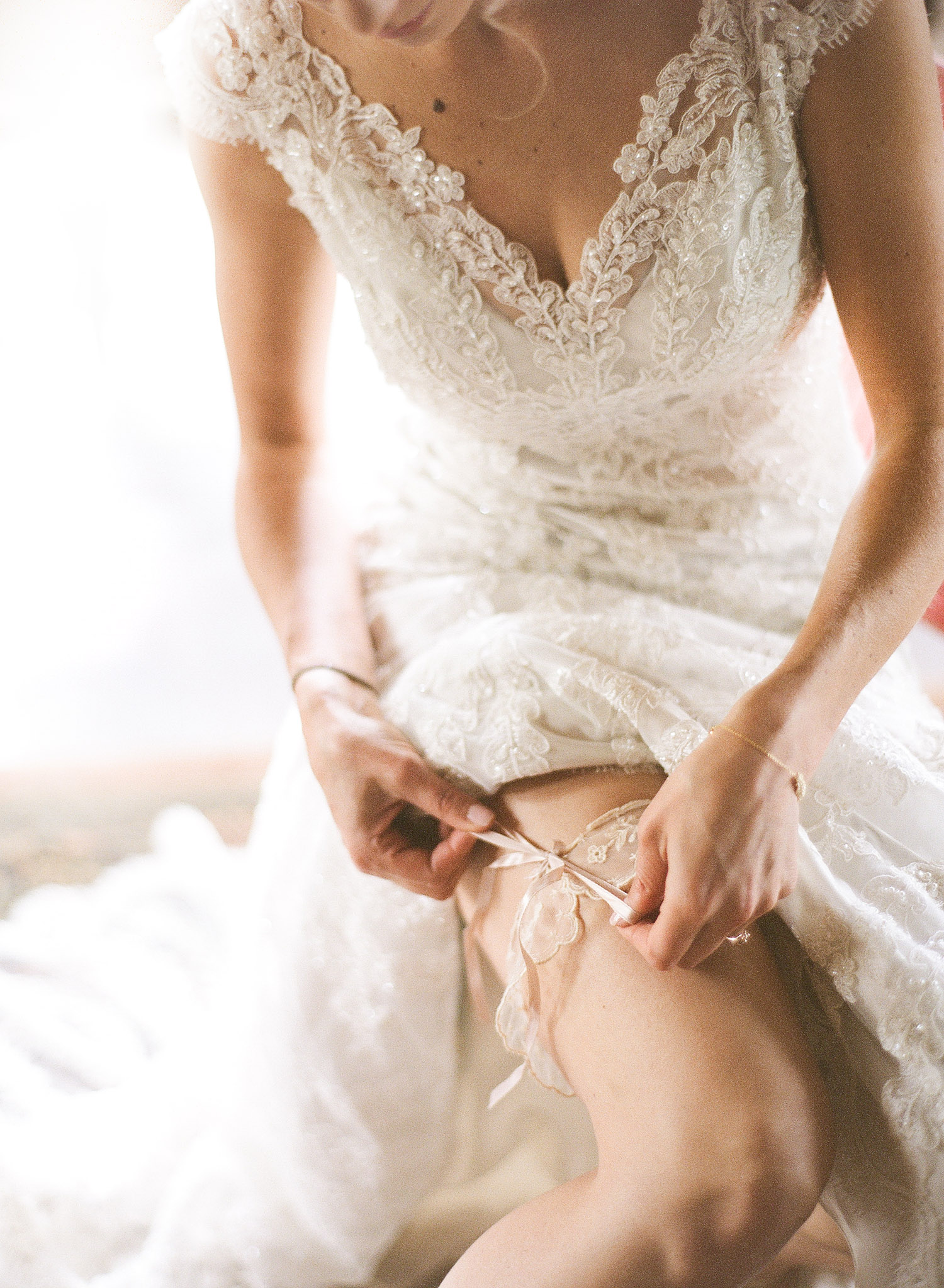 Bride ties on vintage lace garter on her wedding day while destination wedding photographer Lexia Frank photographs this wedding on film at the Northwind Perennial Gardens in Wisconsin