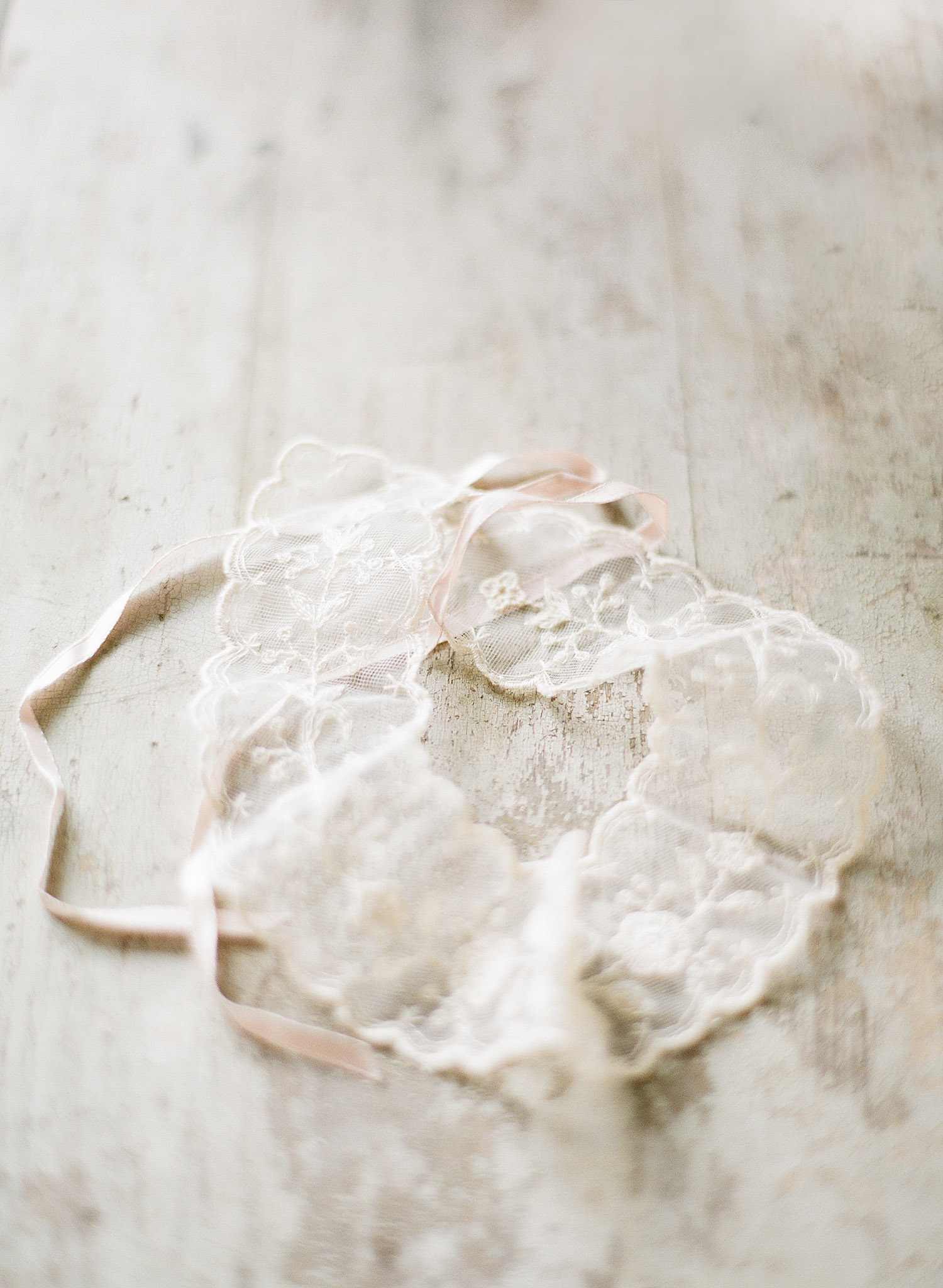 a vintage lace garter lays on a distressed wood table while destination wedding photographer Lexia Frank photographs this wedding on film at the Northwind Perennial Gardens in wisconsin